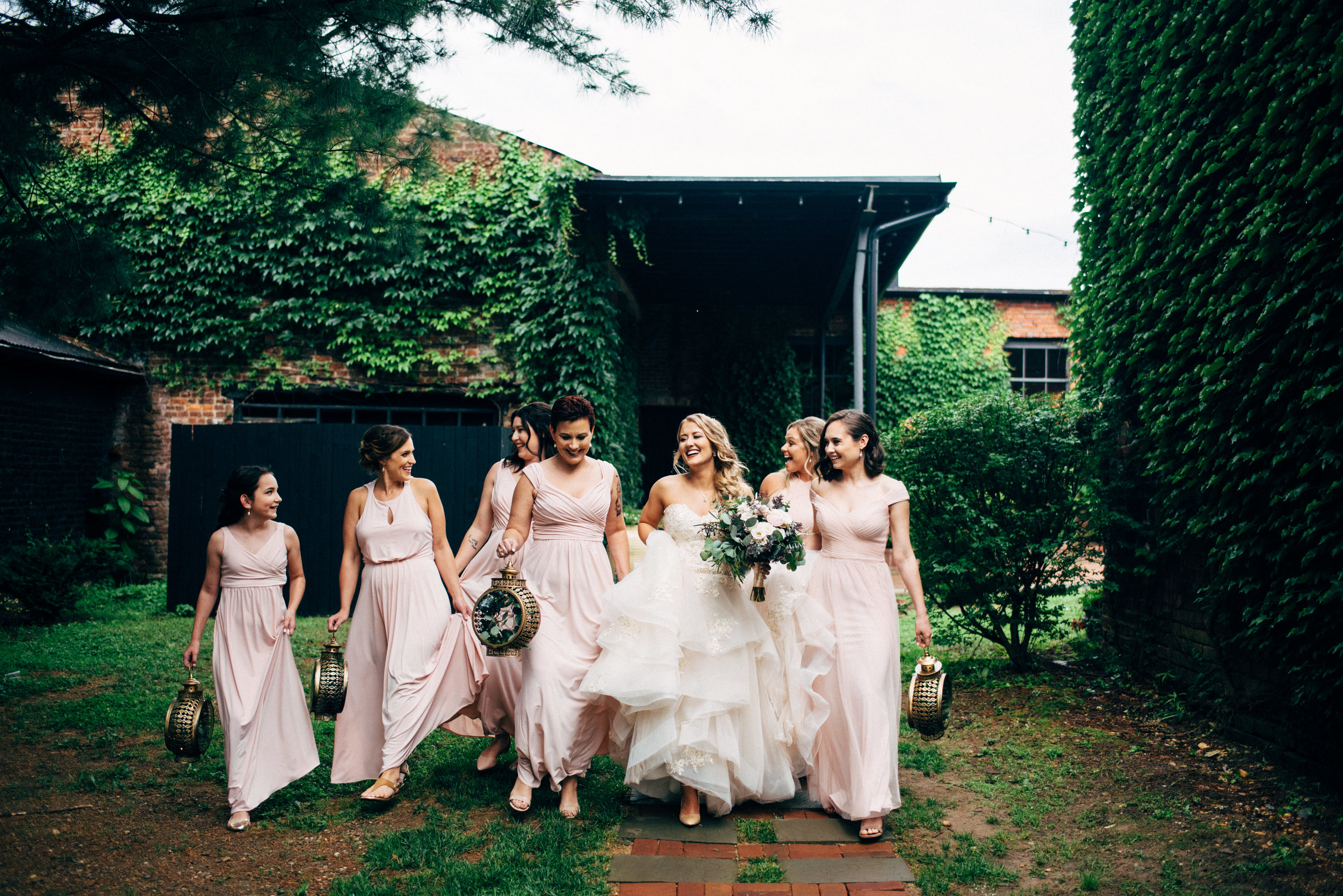 bride laughing and walking down path with her bridesmaids in front of ivy covered building