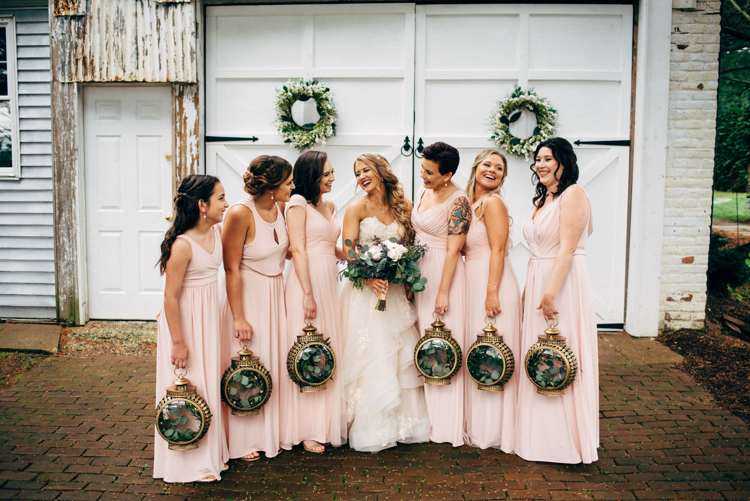bride holding her bouquet and laughing with her bridesmaids