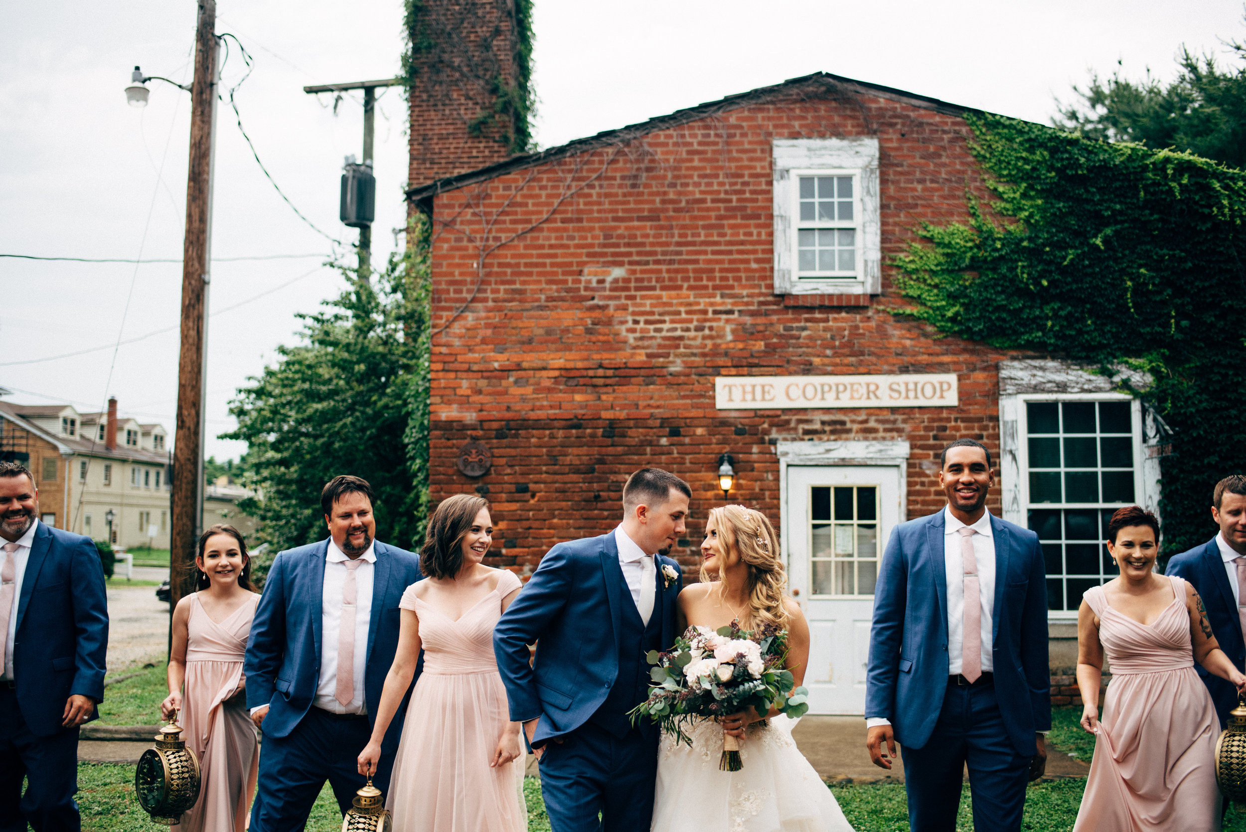 newly married bride and groom look at each other while bridal party looks on