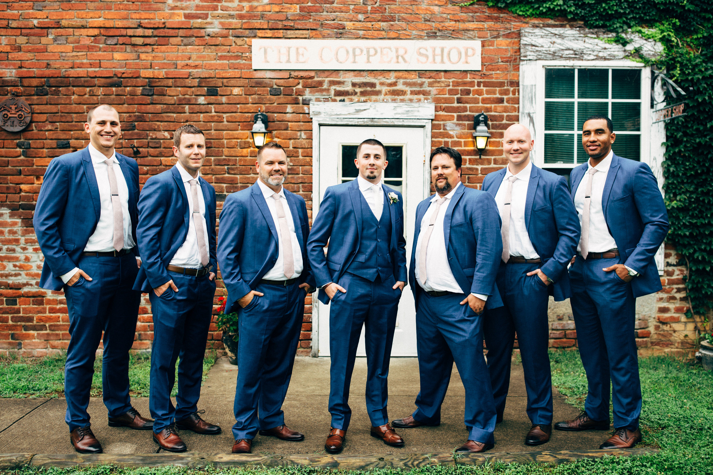 groom with his groomsmen posing in front of brick builing