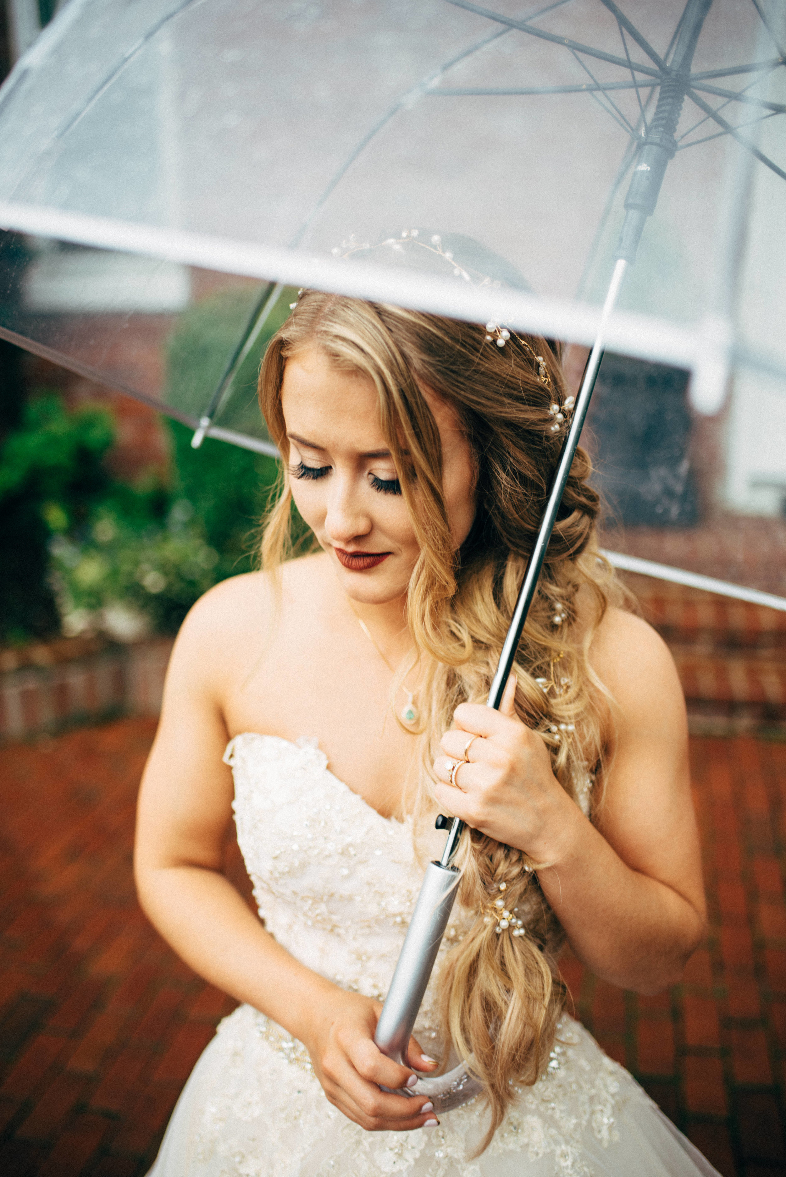 fairy-tale bride in sequined wedding dress holding a clear umbrella