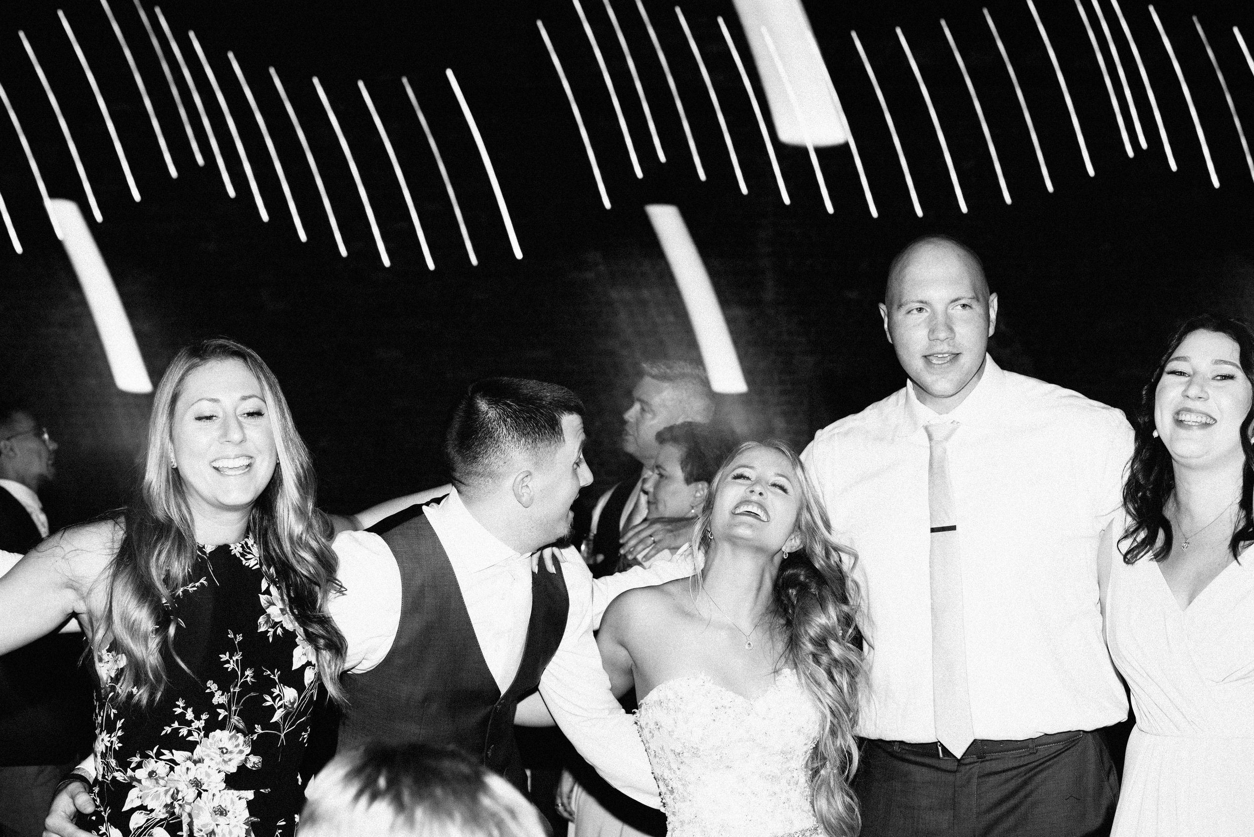 bride and groom dancing with friend's during their wedding reception