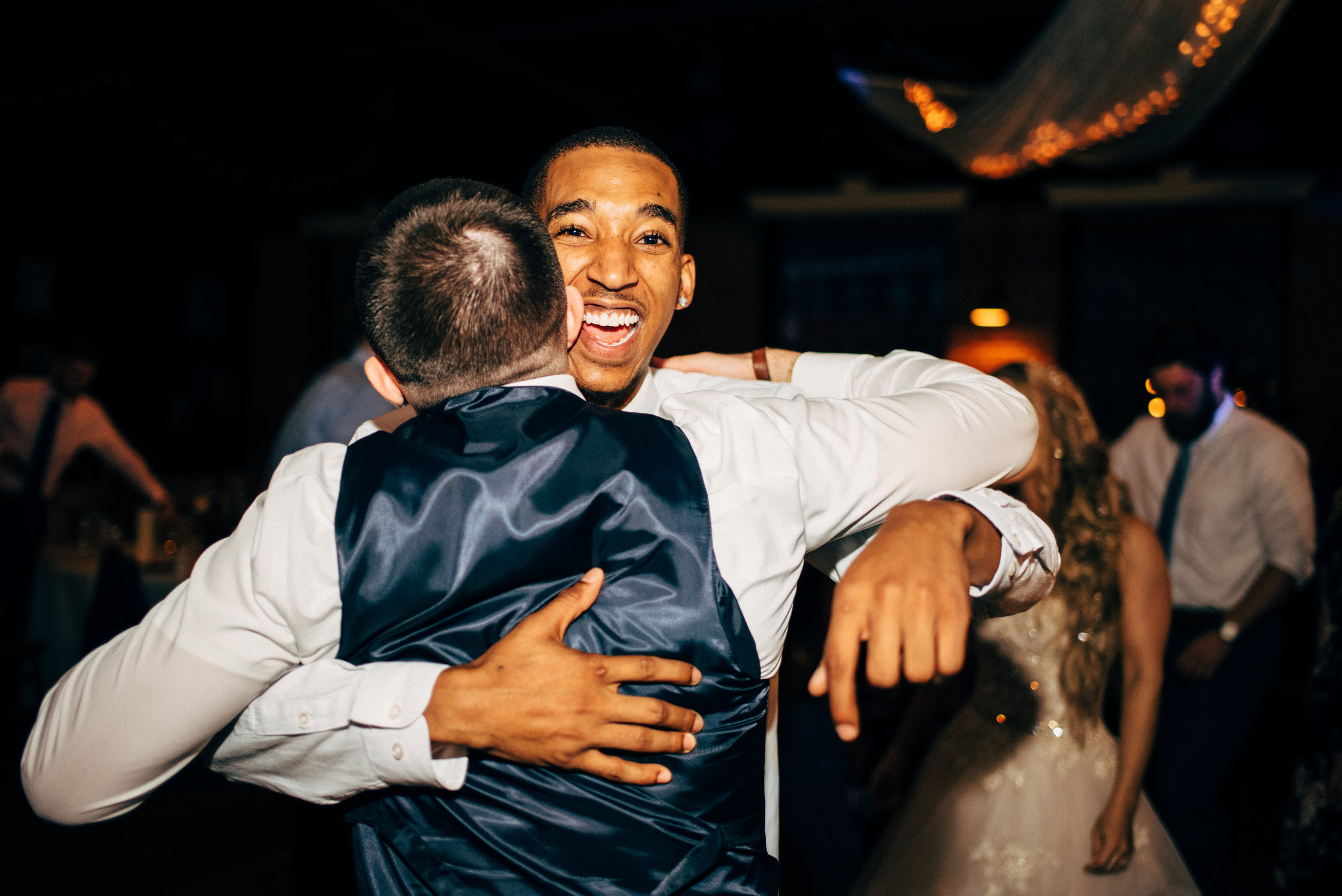 groom hugging his friend during wedding reception at the Inn at the Old Silk Mill