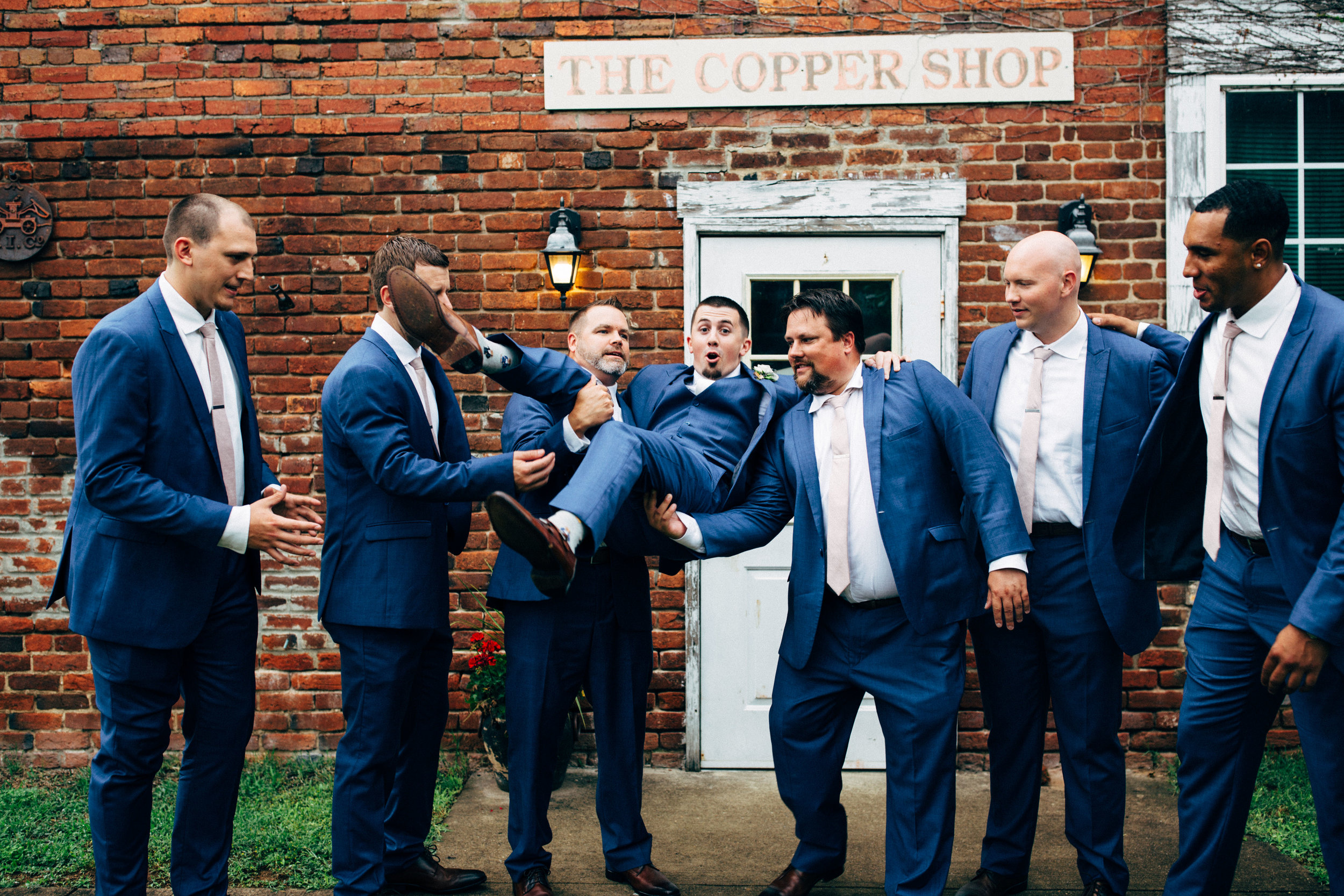 groomsmen lifting up the groom before the wedding ceremony