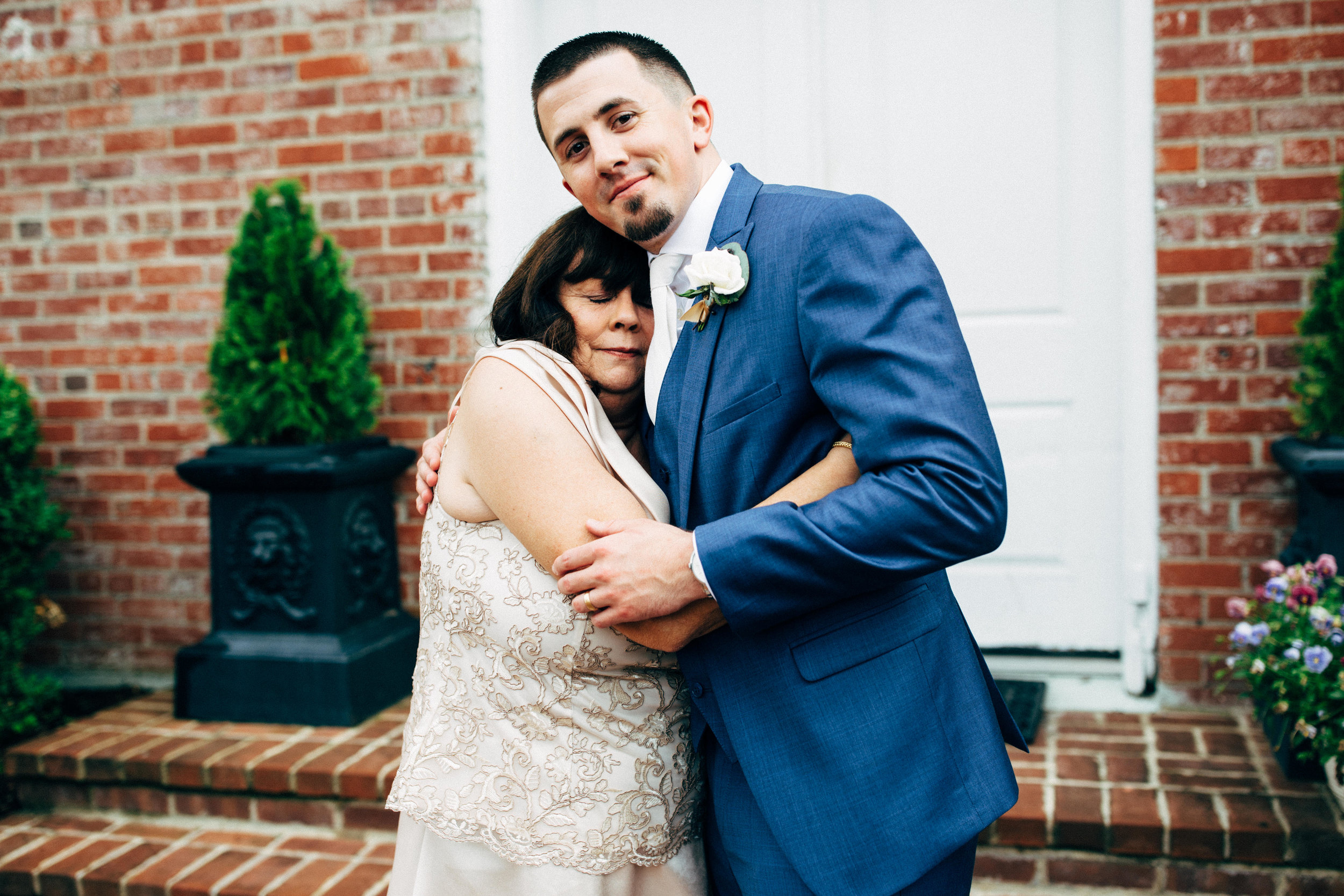 groom hugging his mother and smiling