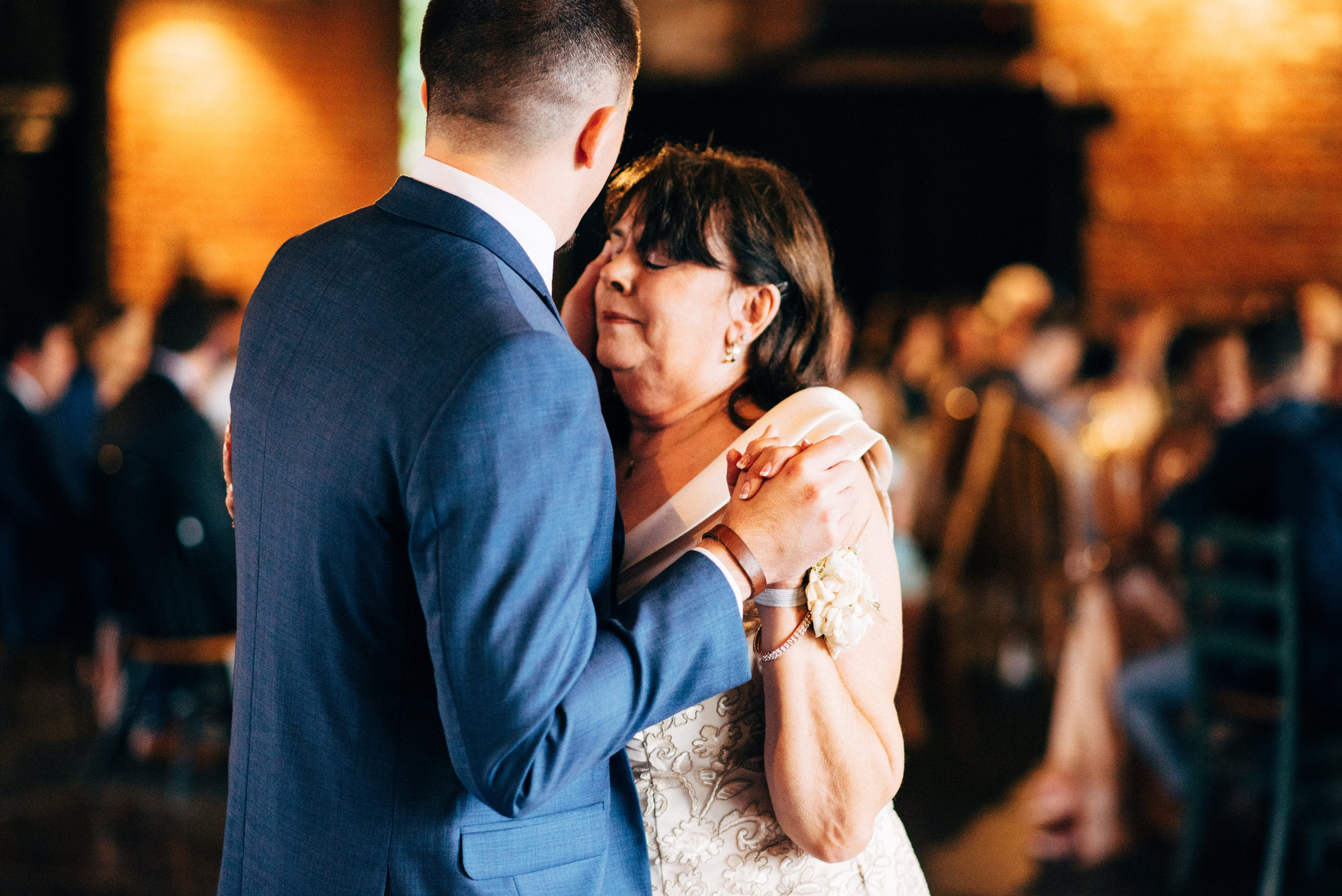 son wipes mother's tears as they dance during the wedding reception at the Inn at the Old Silk Mill