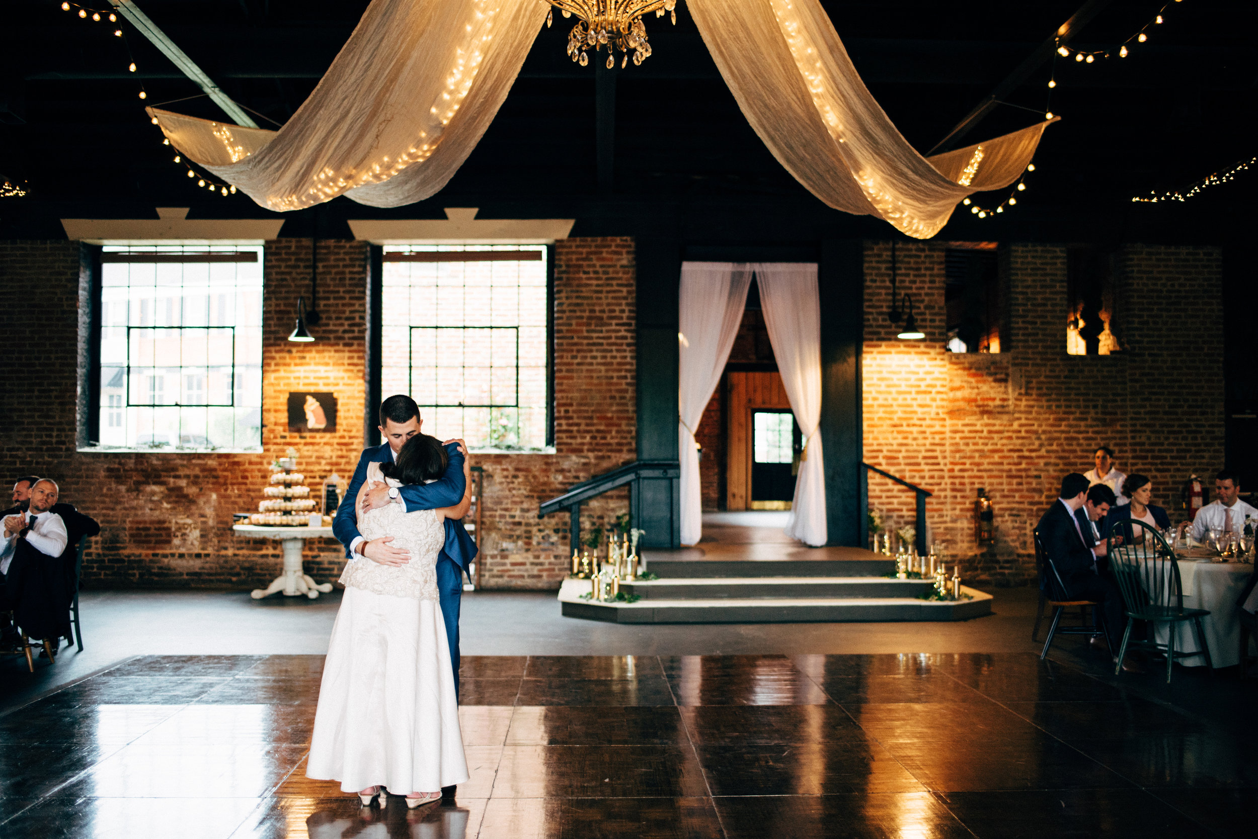 groom and his mother hug after dance during wedding reception at the Inn at the Old Silk Mill
