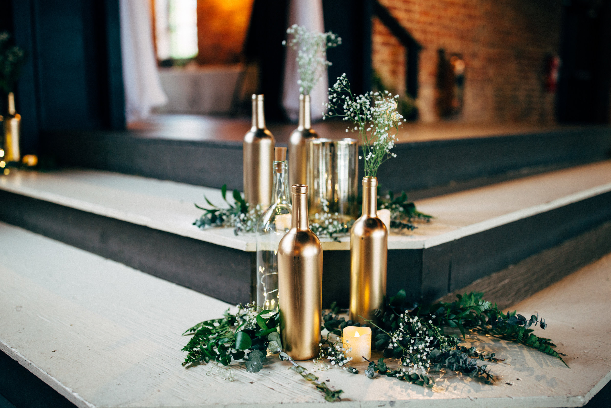 gold bottles decorate the wedding reception at the Inn at the Old Silk Mill