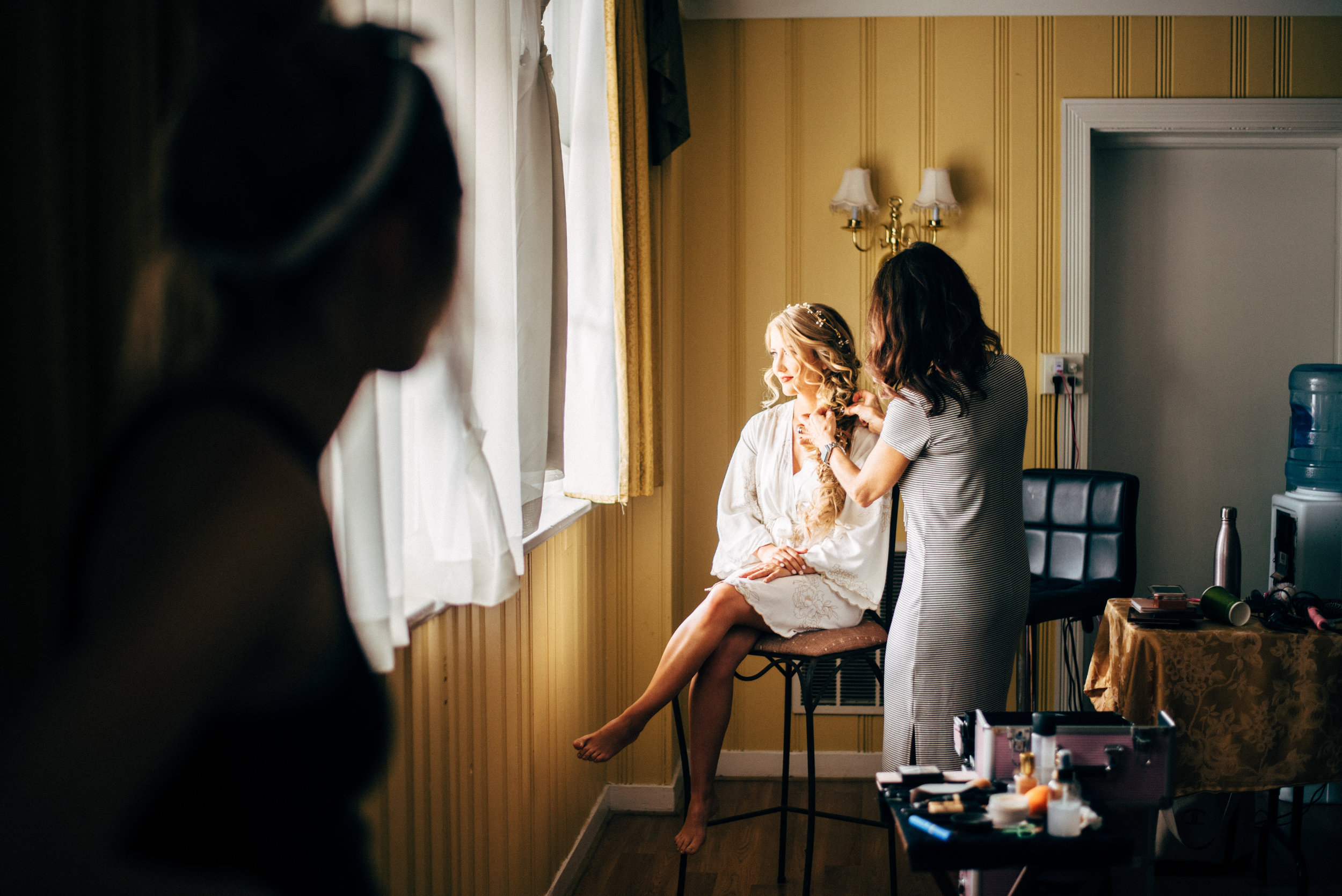 bride looking out the window while hairstylist finalizes her long hair before the wedding