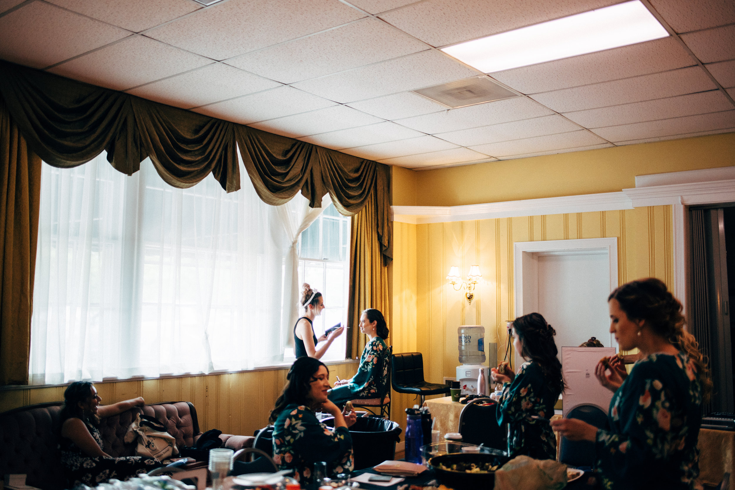 bridesmaids getting makeup done before a wedding at The Inn at Old Silk Mill