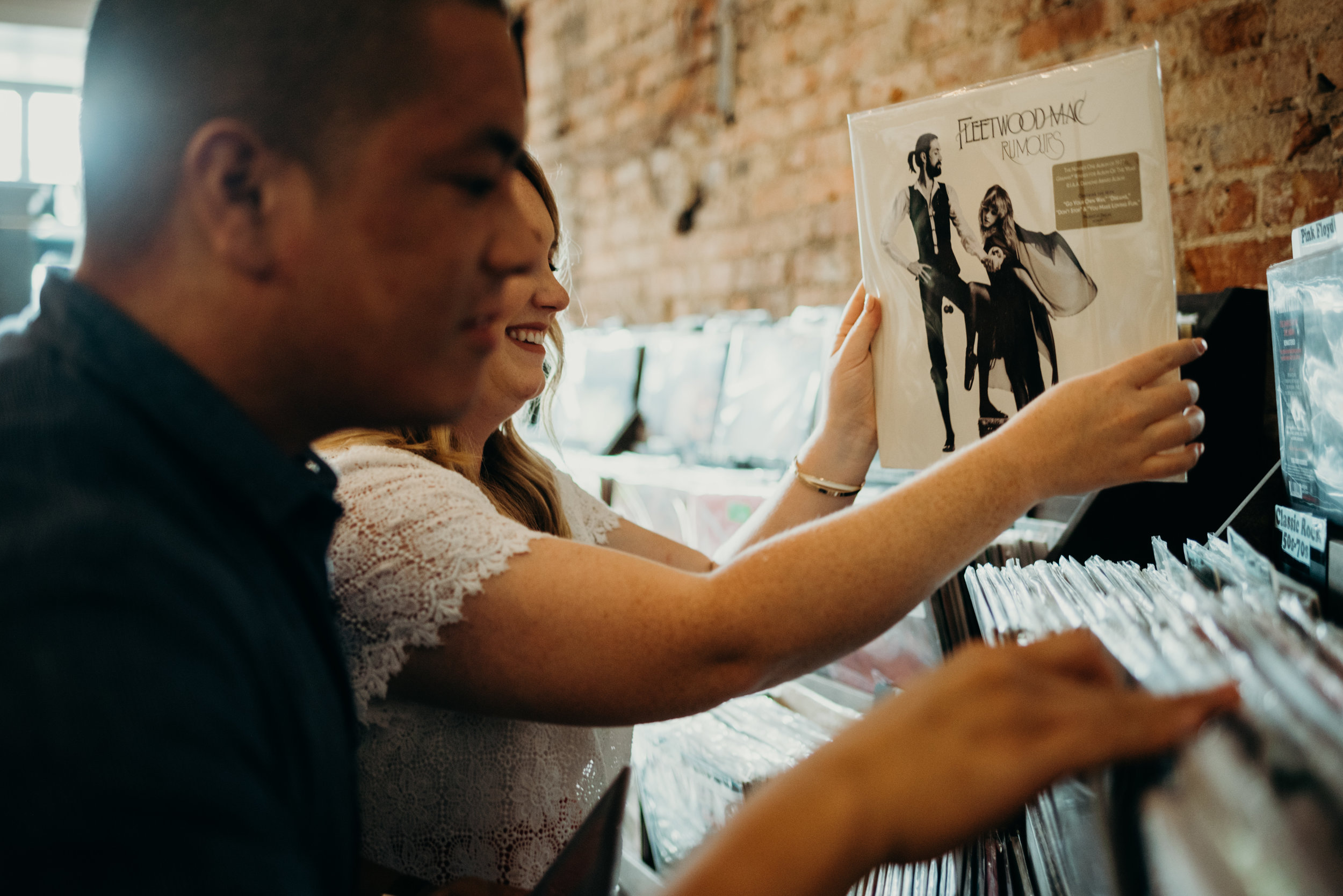 shopping for Fleetwood Mac record during engagement photography session