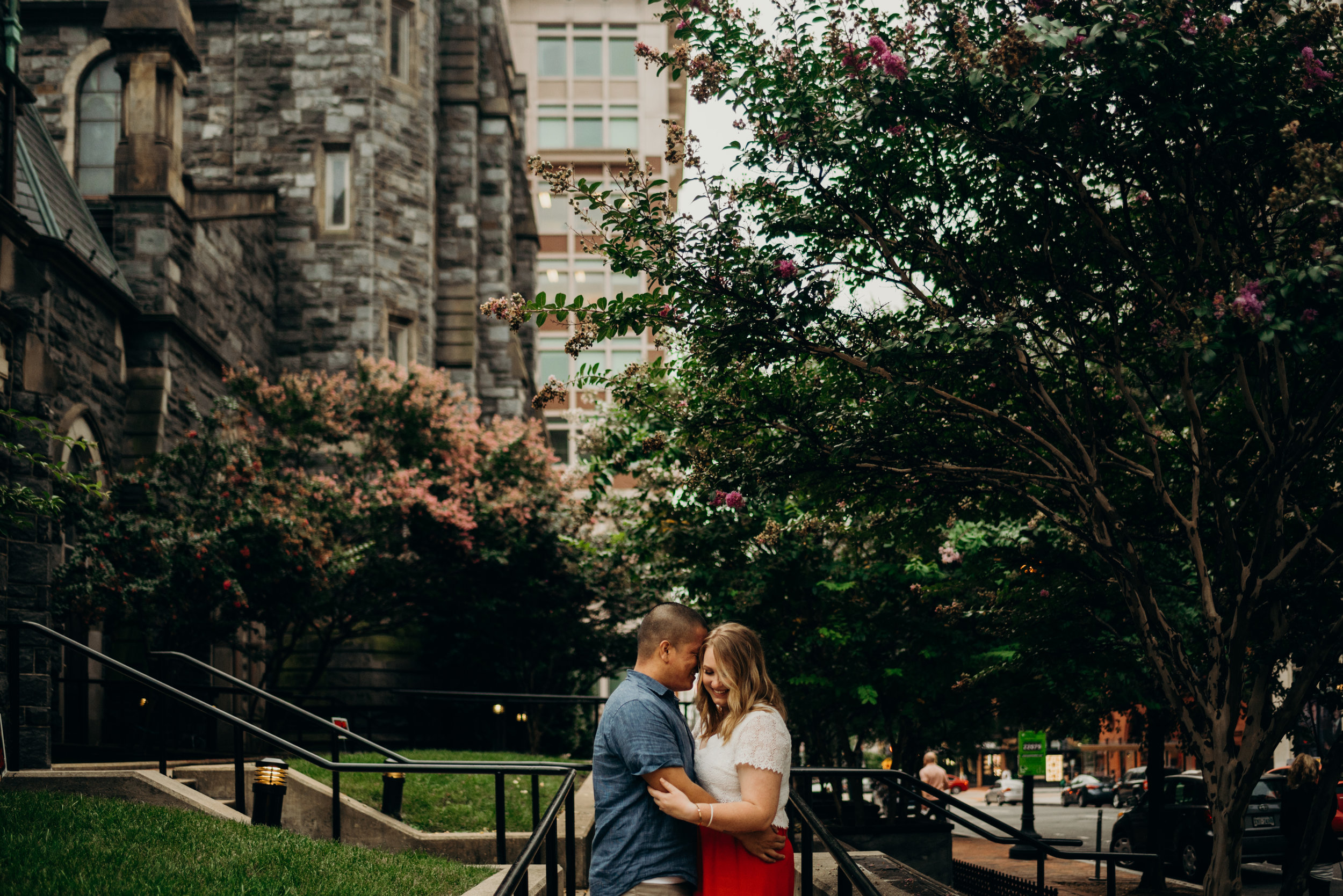engaged couple embracing with trees in the background in Washington, DC