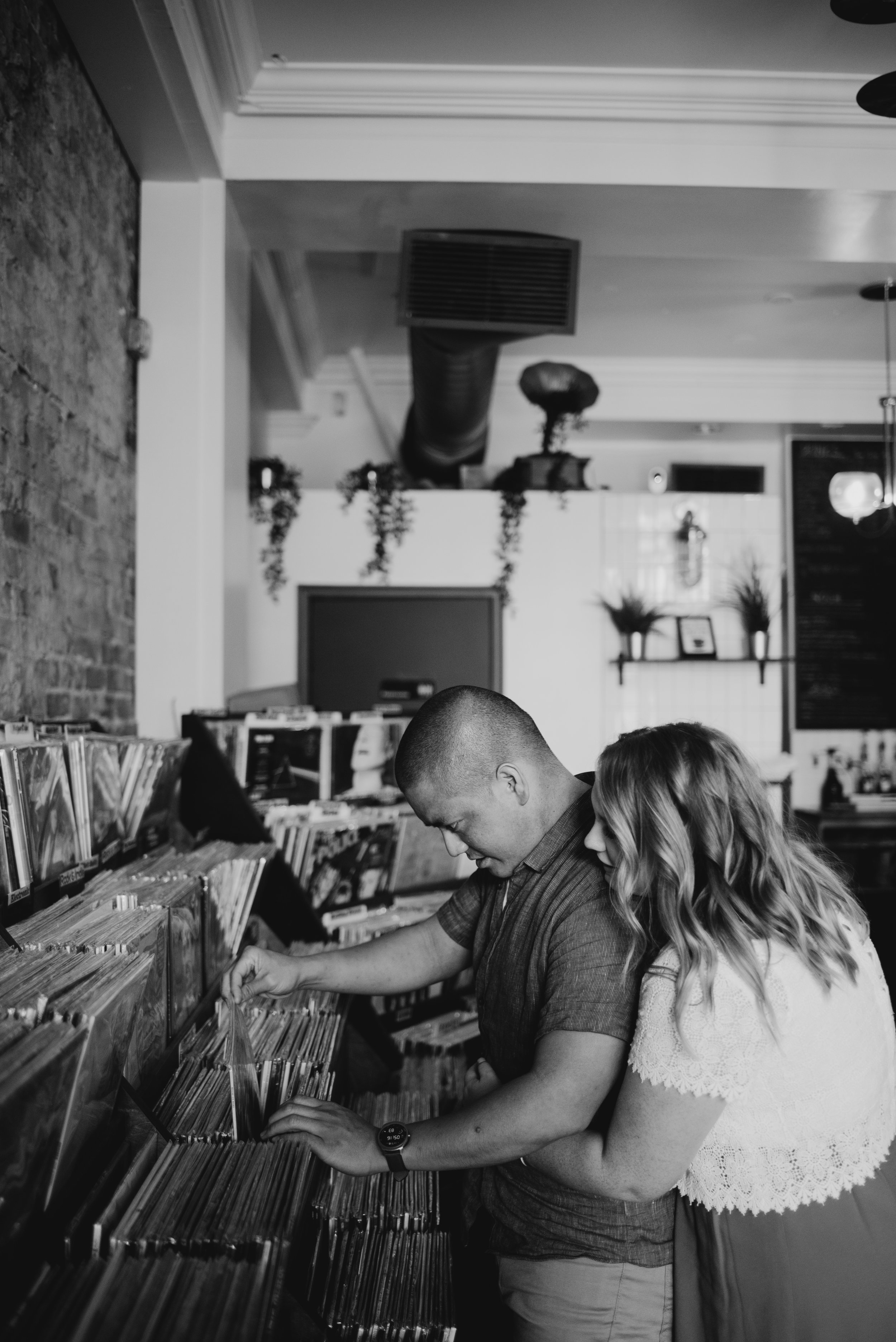 black and white engagement photo of couple at a record store