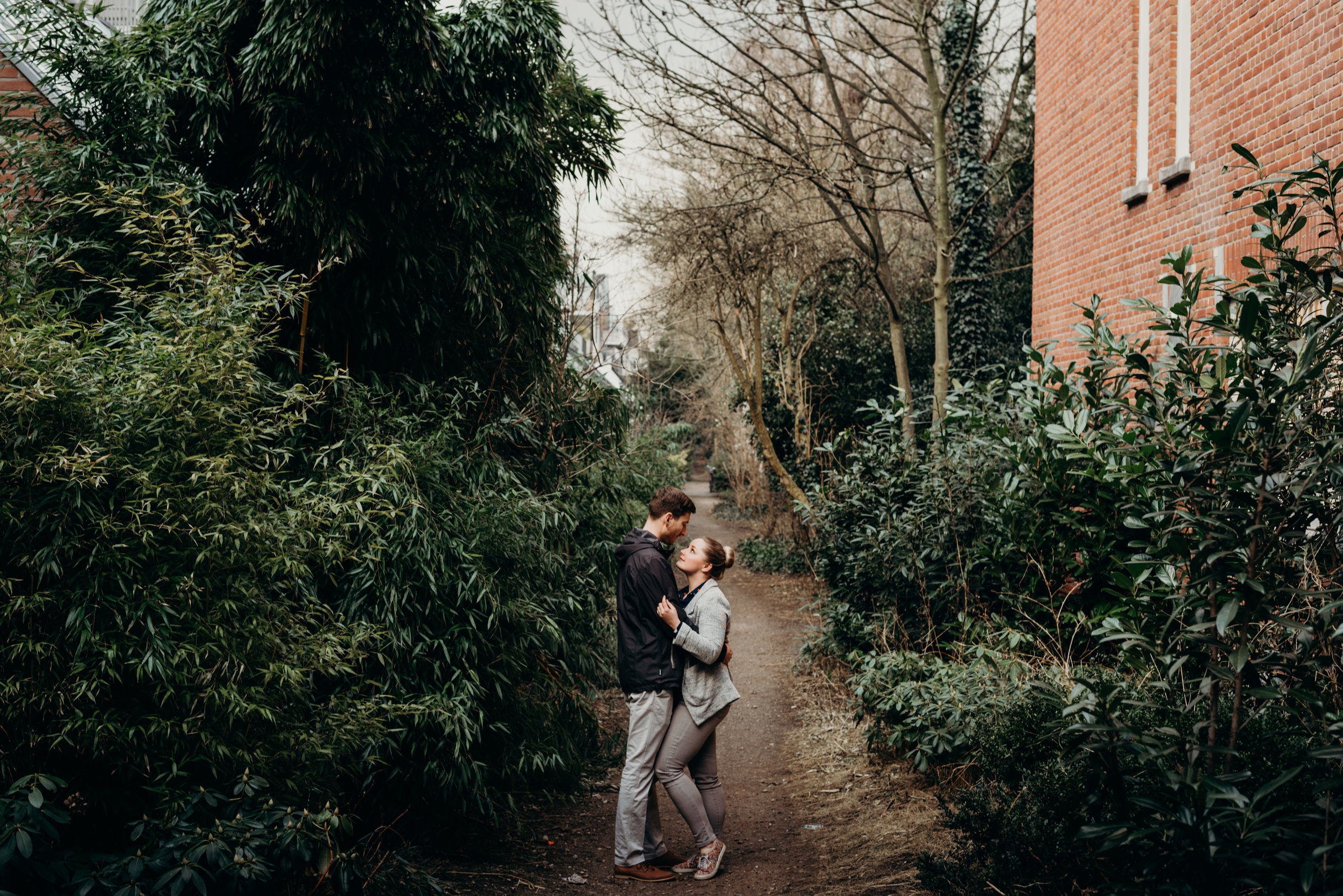 married couple embrace on a path surrounded by trees in Amsterdam