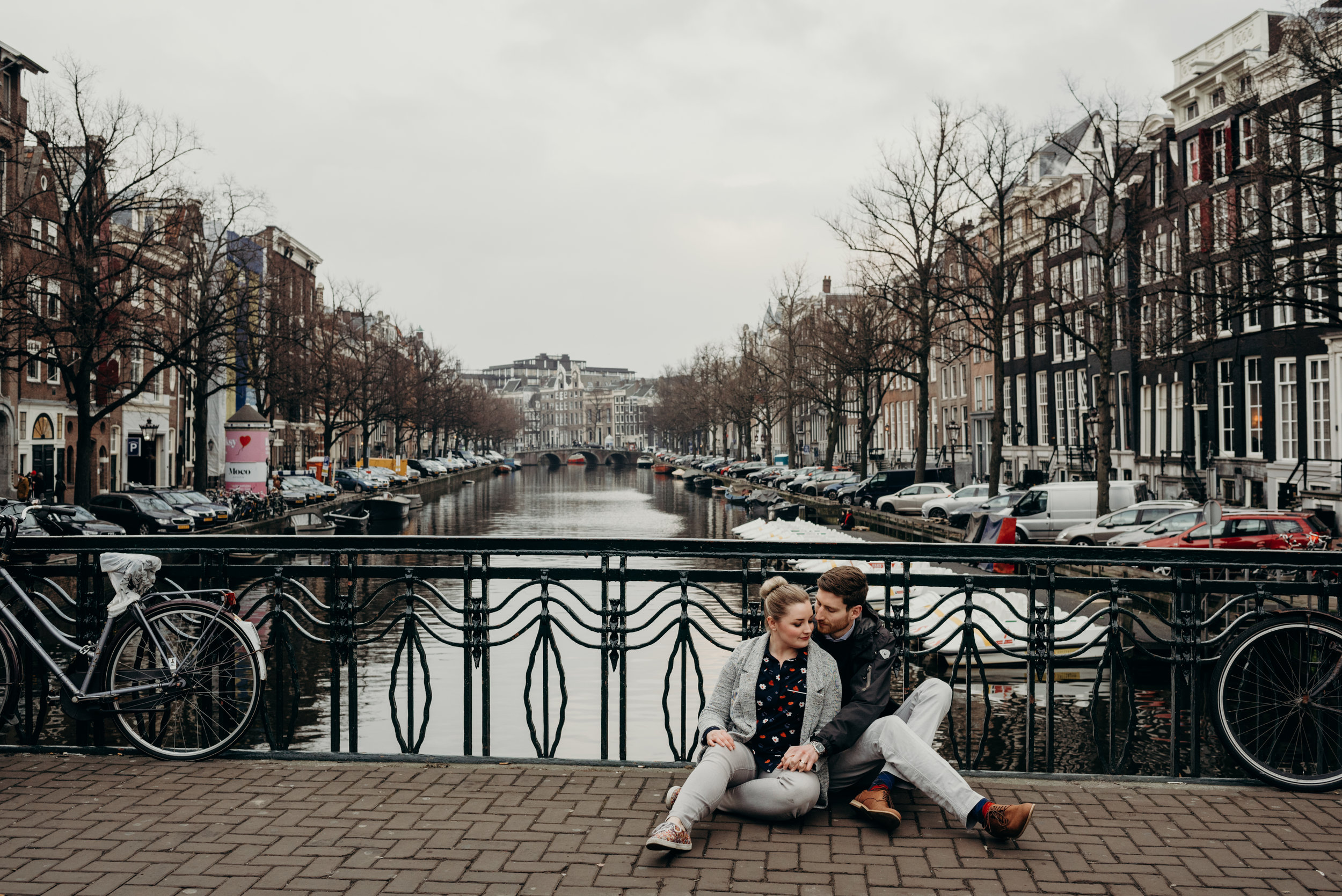 newly married couple sitting on bridge over river in Amsterdam