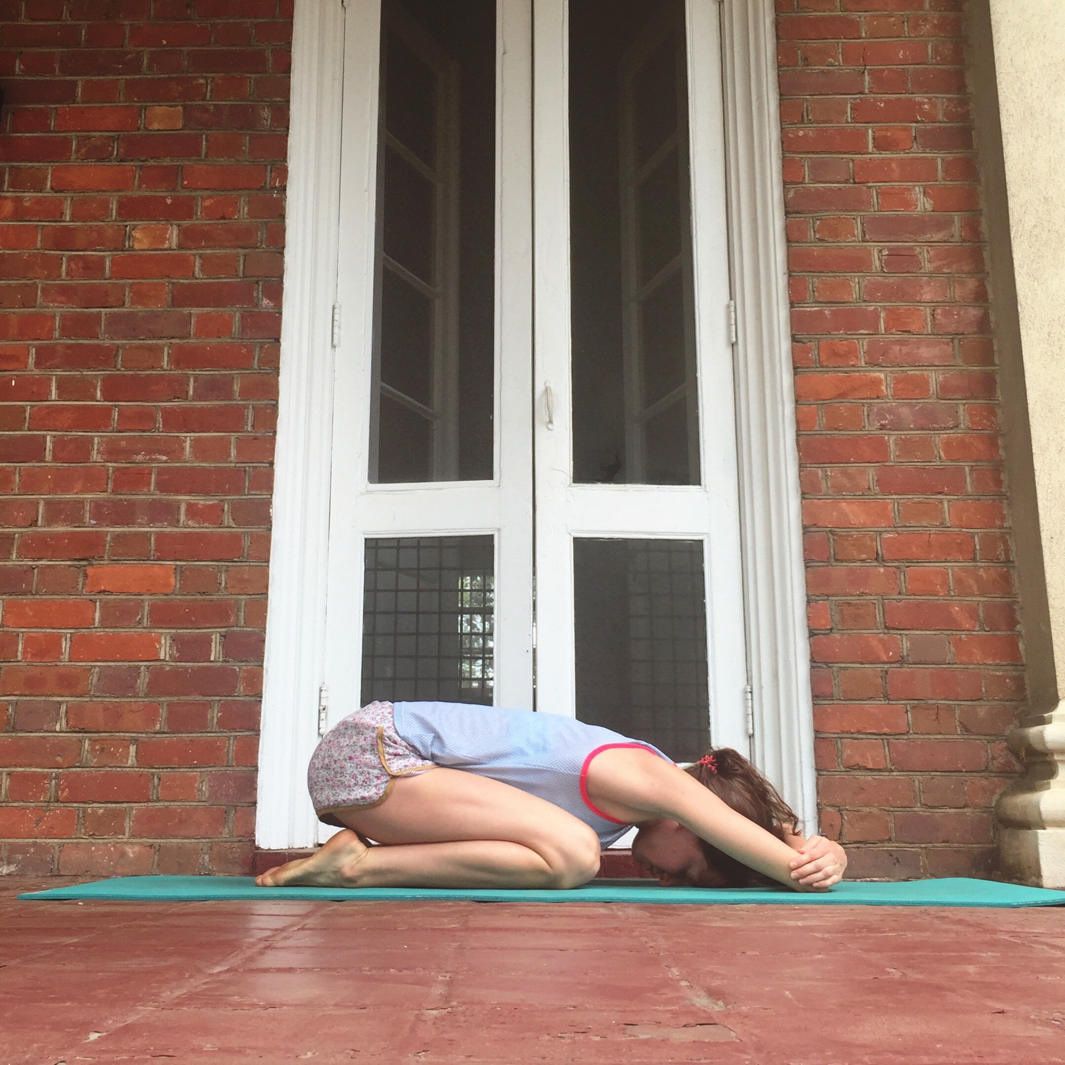 1. CHILD'S POSE WITH ELBOW GRAB.    Sit back onto your heels. Exhale as you walk your palms forward to rest your forehead on your mat. Now grab opposite elbows with your hands. Once you're here, wiggle elbows a little farther away from you. Pause and breathe.