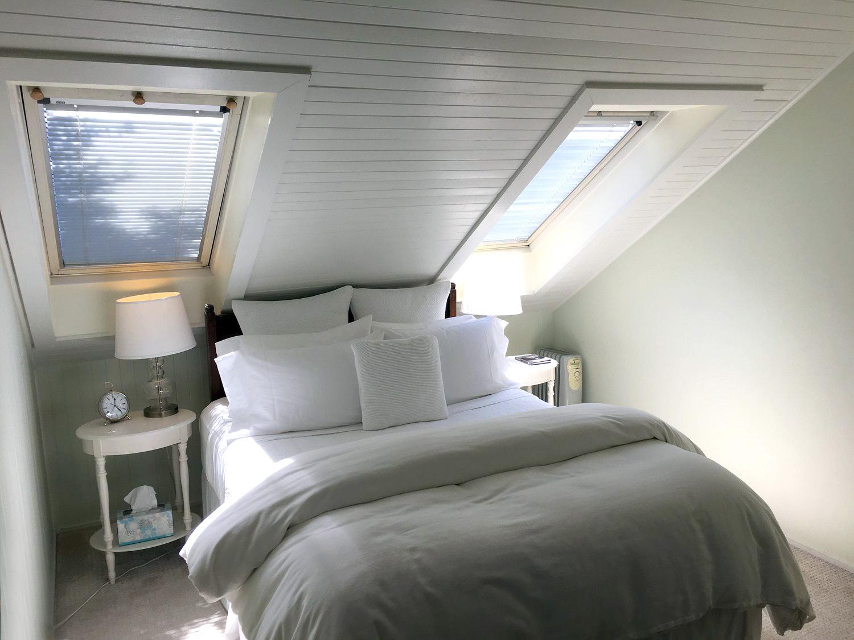 Queen bed under two vaulted skylit windows in sunlight