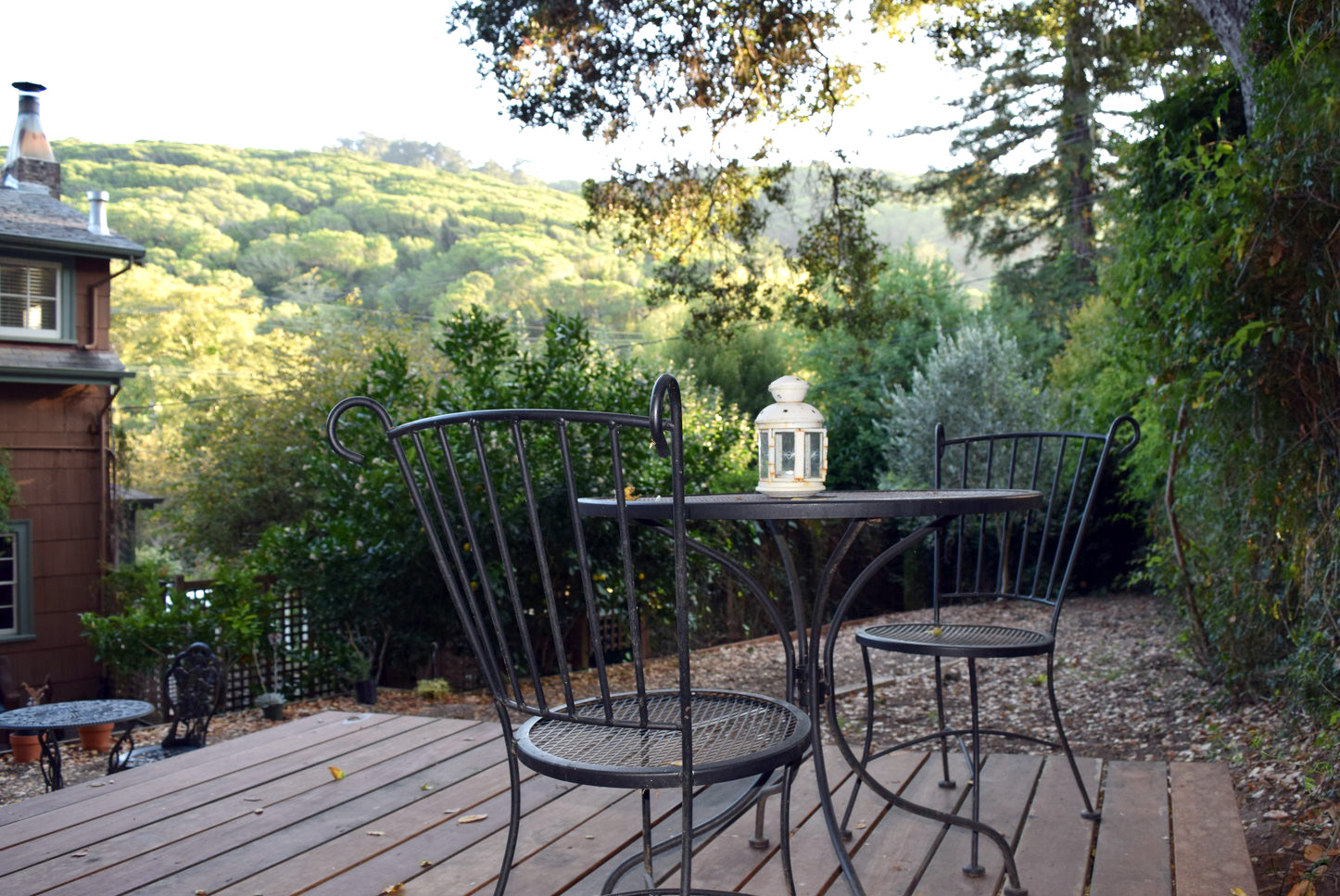 Wrought iron patio seating in private garden and deck with tree covered hill side view