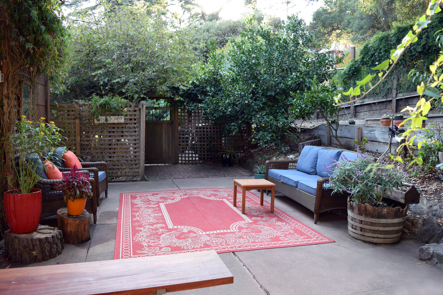 Outdoor patio with seating in private enclosed garden