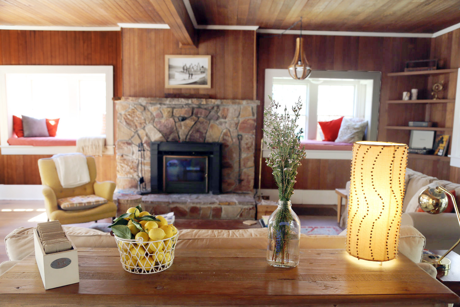 Fruit and floral arrangements on a console table in living room with stone fireplace