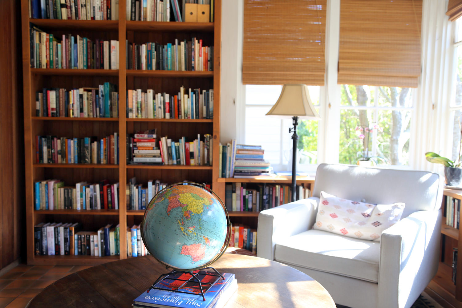 Bookshelves and globe with armchair by brightly lit corner windows