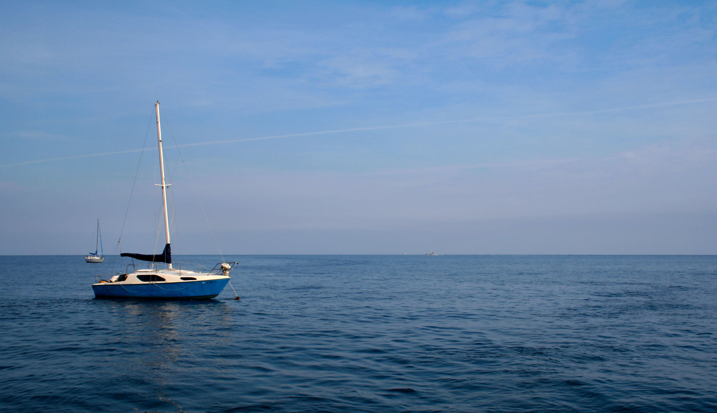 Sail boat in calm water and sunlight against bright blue sky