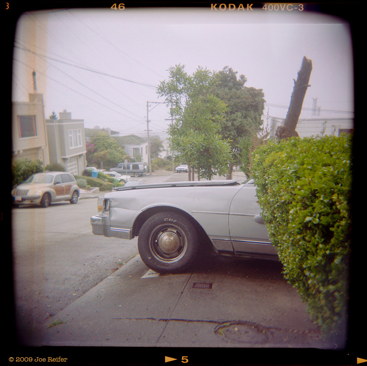 Sidewalk Conundrum with Broken Mirror and Faux Wood P.T. Cruiser -- by Joe Reifer