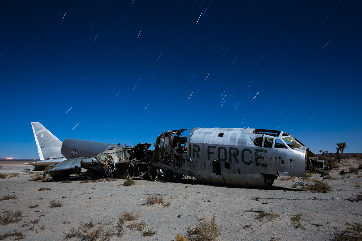 An old Air Force B-52 bomber lies in pieces in the Mojave Desert under a full moon and star trails.