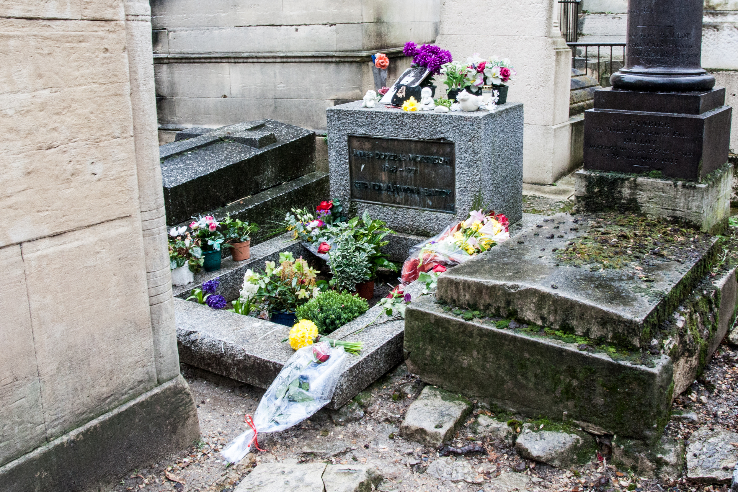 Jim Morrison's grave, protected by chainlink fence and security guard.