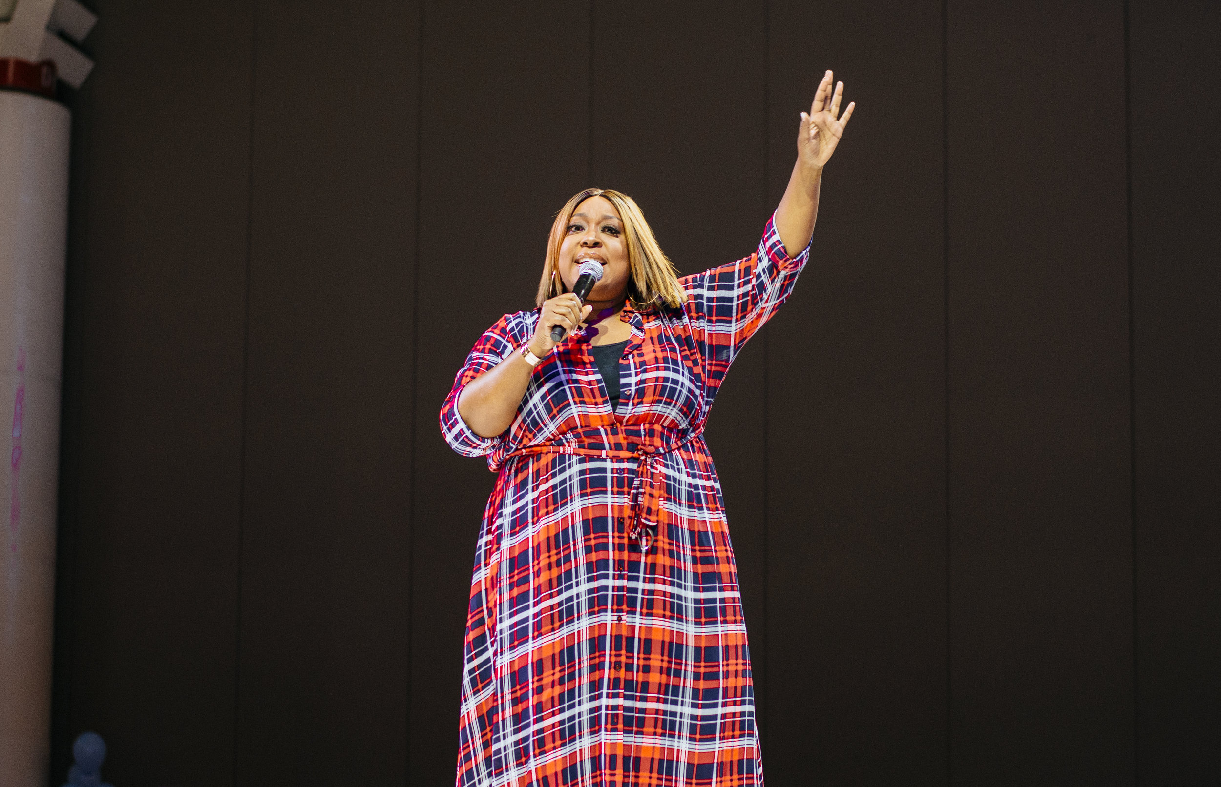 Loni Love waving to the crowd as she introduces the next act.