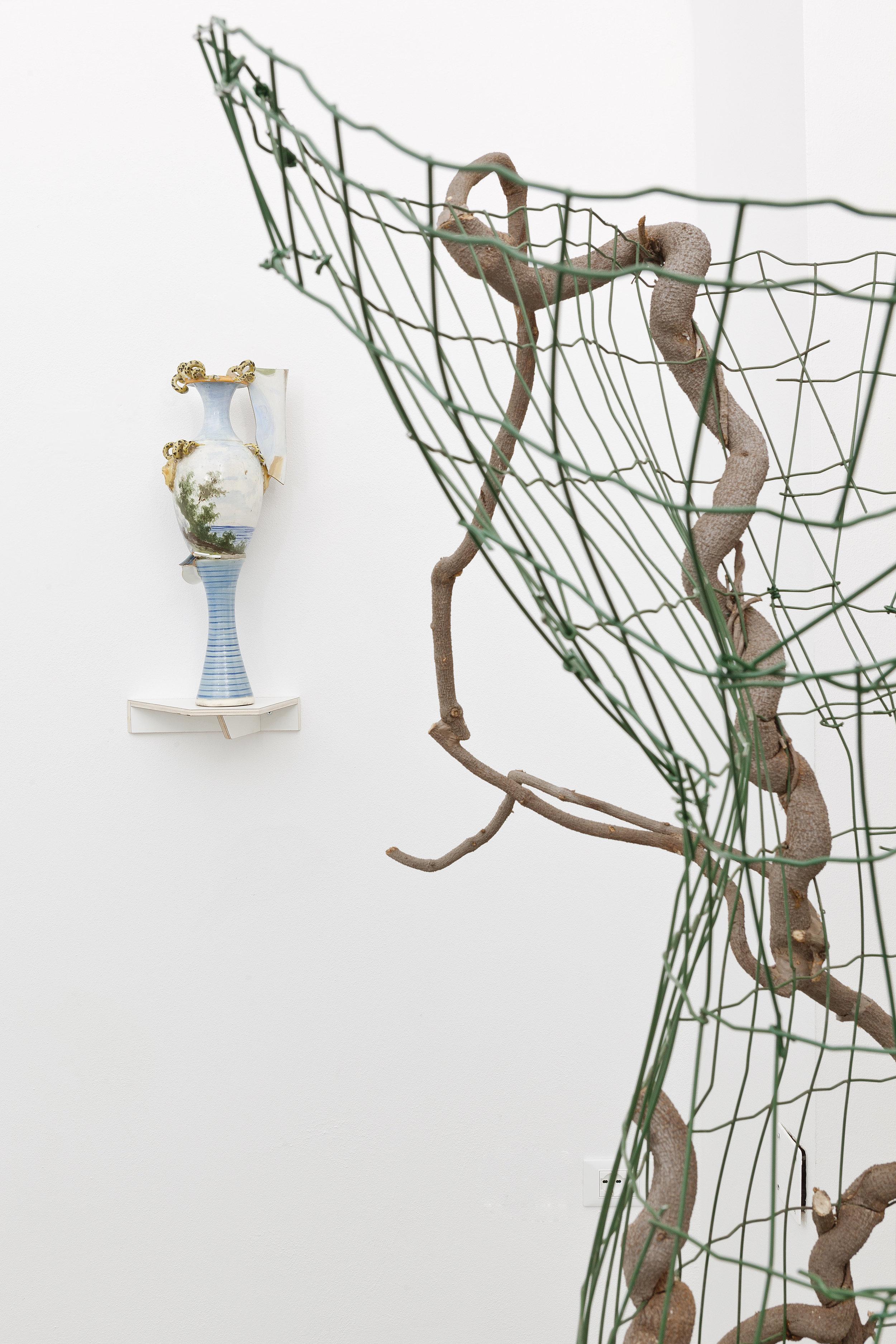 Lei / Wisteria  (dettaglio) 2018 - Rete da recinzione, glicine e pietre - cm 180x97x77. In secondo piano: B. Meoni -  Florencia  2018 - Porcellana - cm 50x20x18