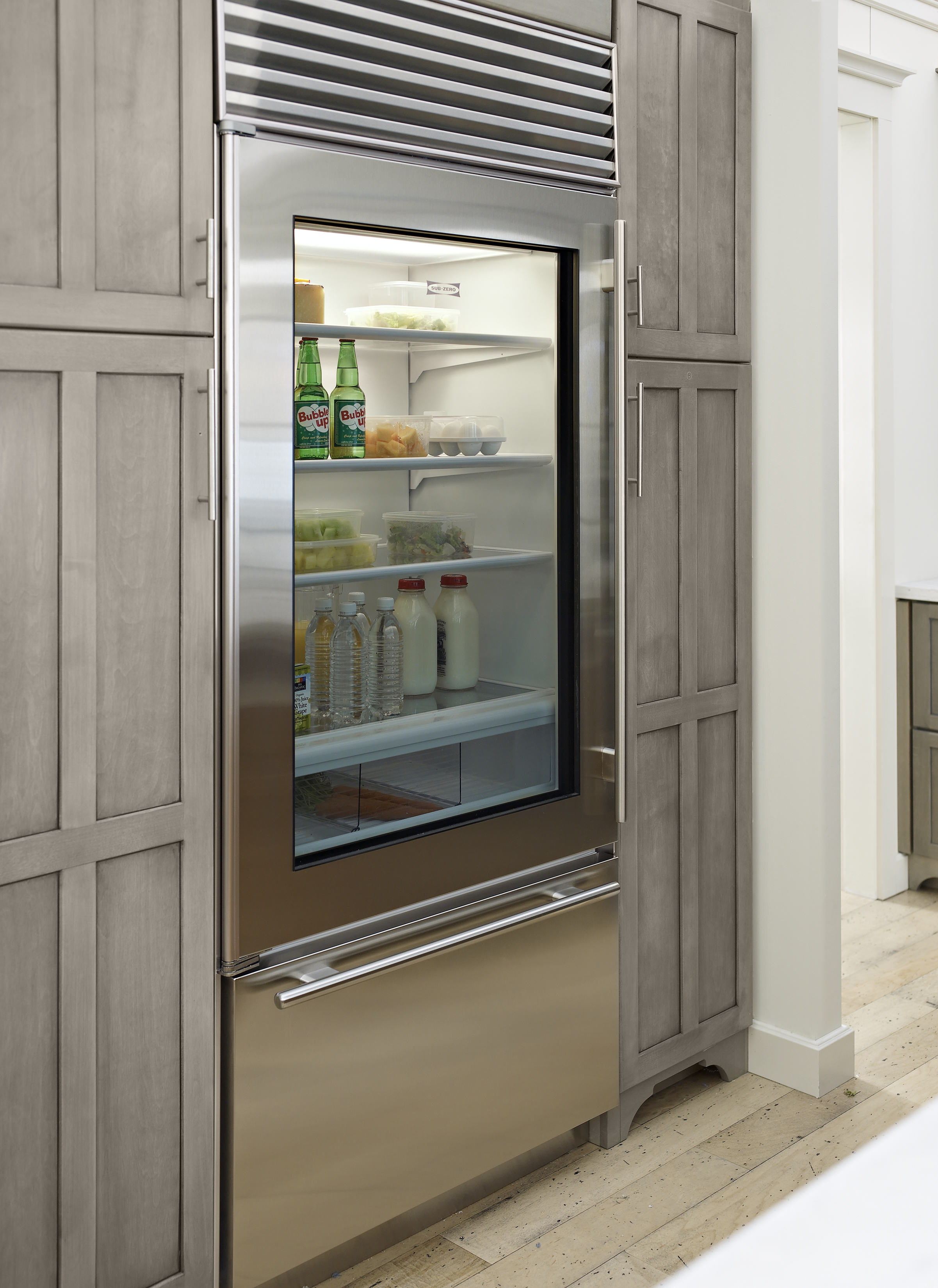 Stainless steel fridge fitted between wooden cabinetry along the kitchen wall