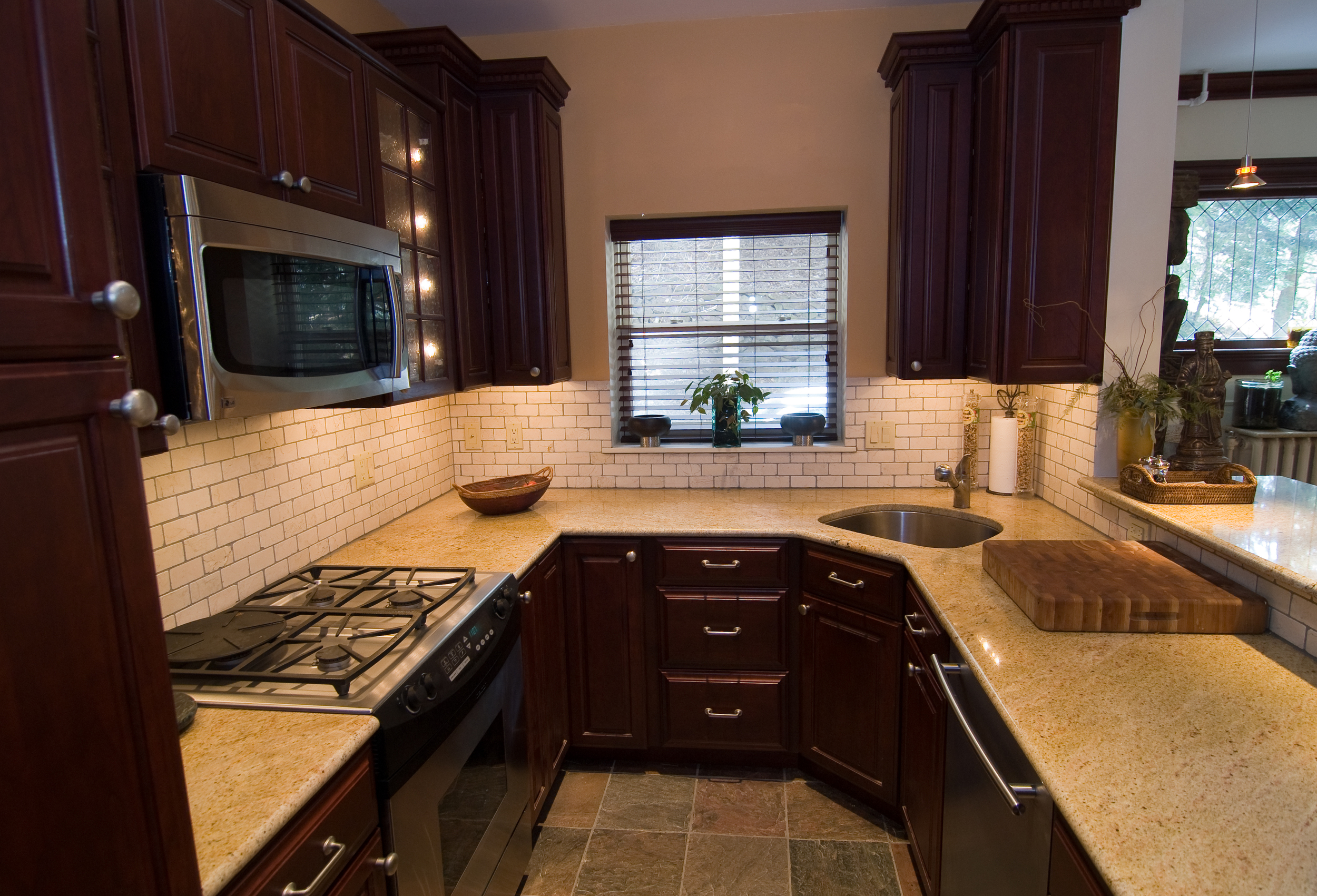 A perfect contrast of dark cabinetry and light earth toned countertop for this small kitchen space
