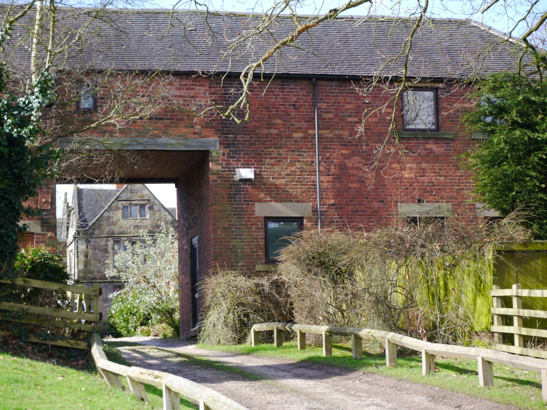 View of Padley Hall through Padley Mews barn conversion