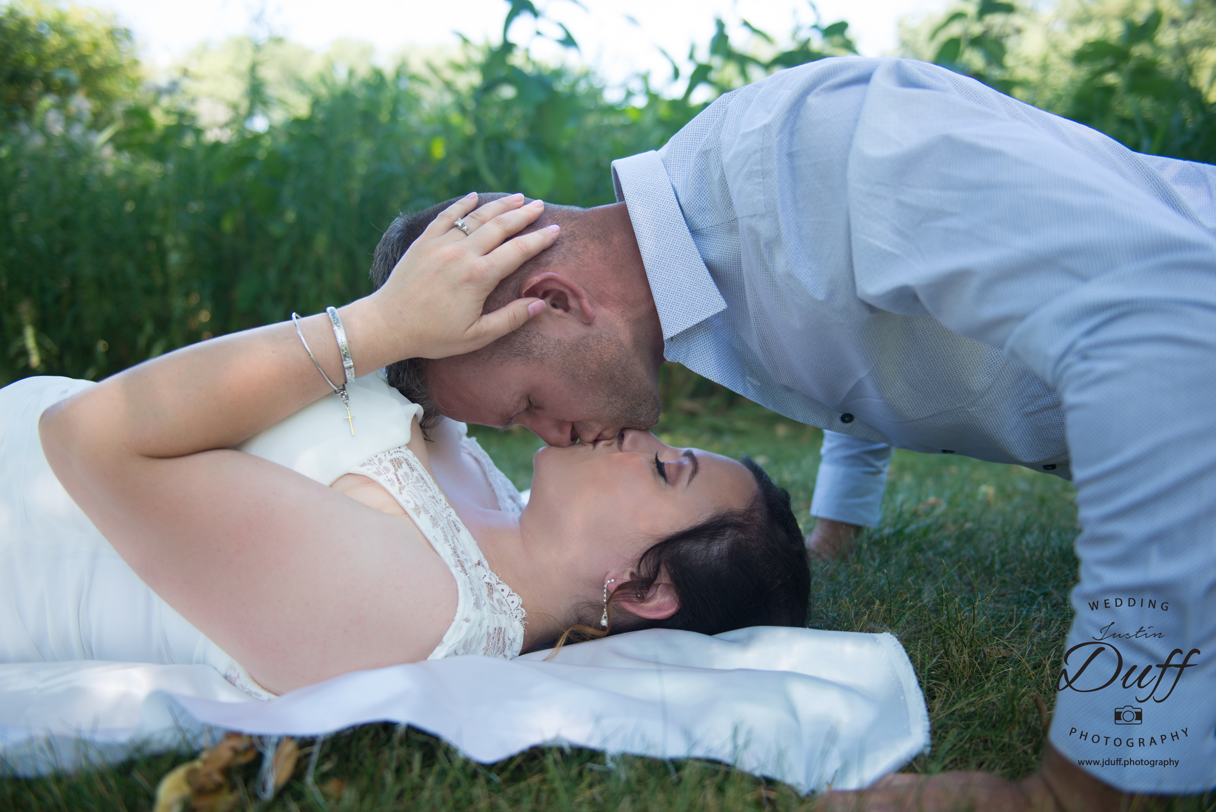 Firefighter Park Wedding - Troy MI wedding photographer. Bride laying on grass. push-up kiss. spider man kiss.