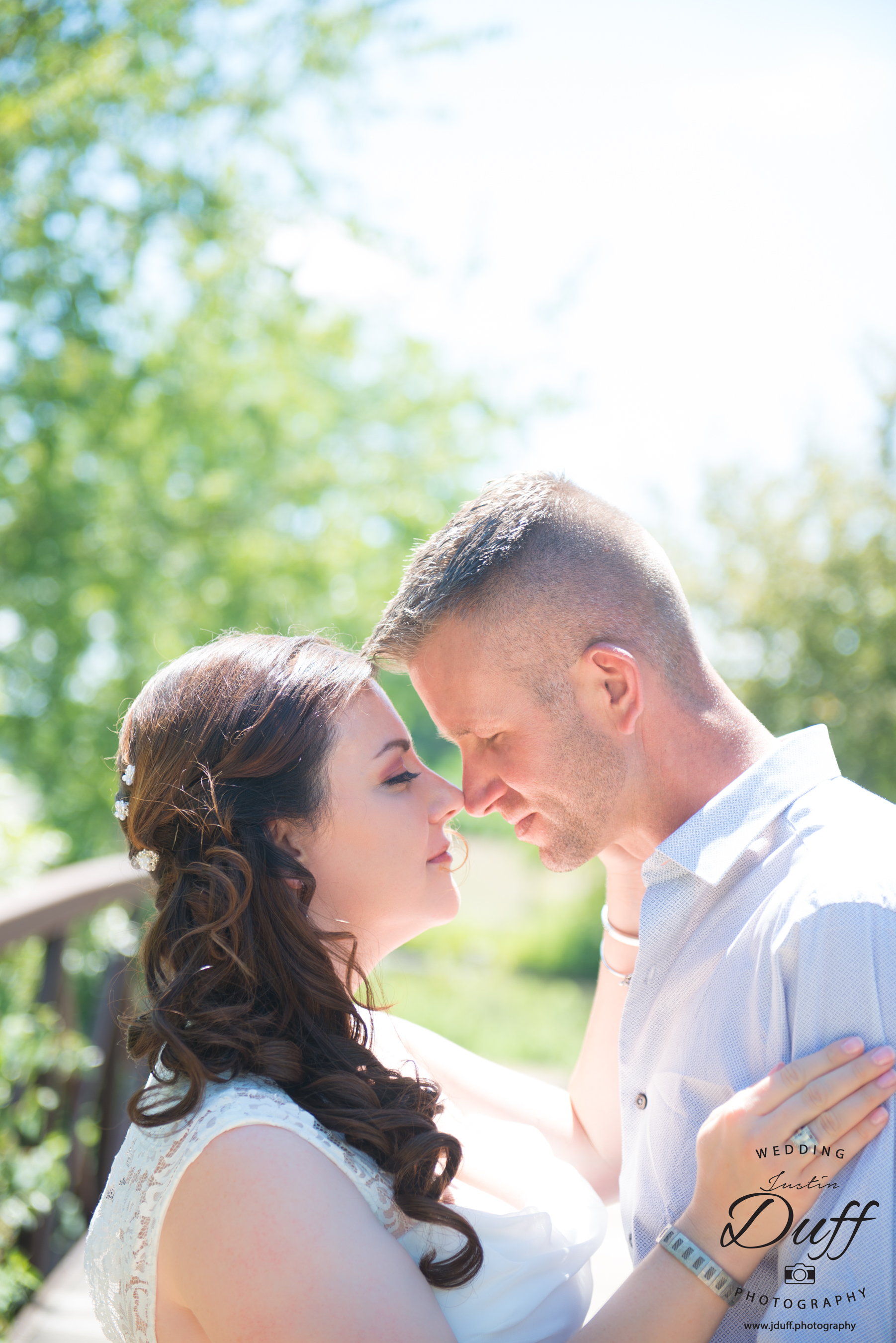 Firefighter Park Wedding - Troy MI wedding photographer. Bride and groom on a bridge touching noses.