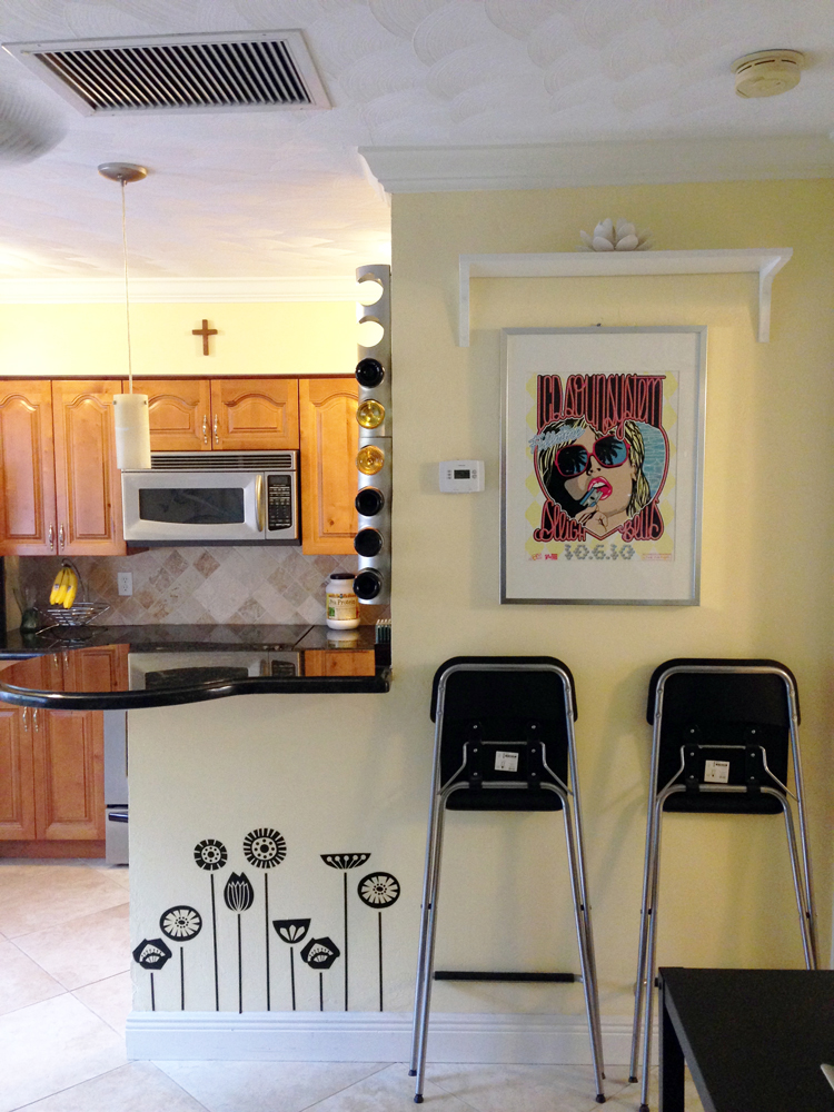 Kitchen    The round counter functions as a dinette. Those foldable chairs from IKEA are easy to set up when I need them, and store flat against the wall when I don't. And a wine rack fit nicely on that skinny slice of wall. The music posted was designed and screen printed by a friend of mine.