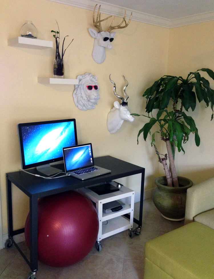 """The """"Office""""     Thanks to modern technology, you don't need a ton of square footage to create a workspace. The rolling desk and cart from CB2 make this setup modular and the workout ball doubles as a bouncy yet comfy seat. (Or sometimes I just pull up the ottoman and sit on that.) The desk is big enough to accommodate my laptop, monitor and my tablet and other less frequently used items like the scanner get stored on the cart underneath.    Then there's my quirky, vegan safari collection on the wall. (Counter-clockwise from top: Office Antlers, Hudson the Hipster Lion and Kudisha the Kudu.)"""