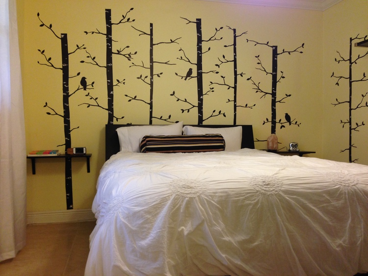 The Bedroom     I wanted something whimsical that I would love waking up to each morning so I went with a slightly enchanted forest theme. The headboard has storage compartments for housing chargers and books and mounting shelves on the wall instead of using side tables makes the space feel larger and less cluttered.    I love bright, white hotel-style bedding so I opted for a subtle, white, flower-embroidered duvet that wouldn't clash with the busier wall design.