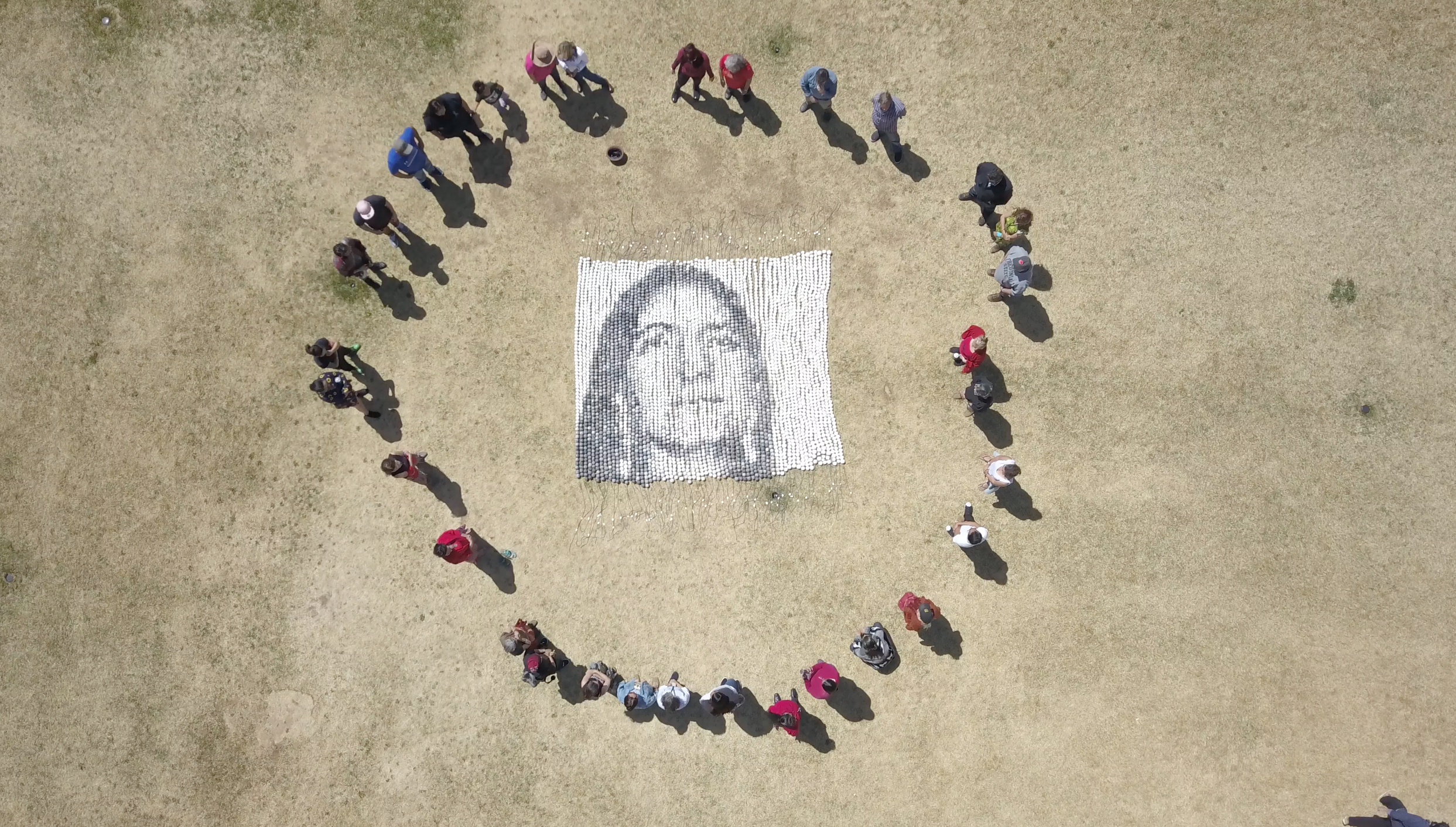 "12' H x 12' W beaded portrait using over 4,000 single 2"" clay beads   Every One . Social collaboration, sculptural installation. Cannupa Hanska Luger 2018.  Image: Red Shawl Solidarity Society prayer action at the Institute of American Indian Arts, Santa Fe, NM April 26, 2018"