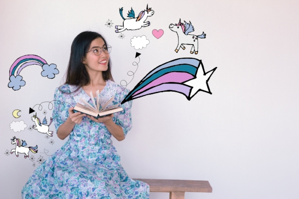 Young asian woman reading A fairy tales book with unicorn and rainbow illustration doodles- imagination concept