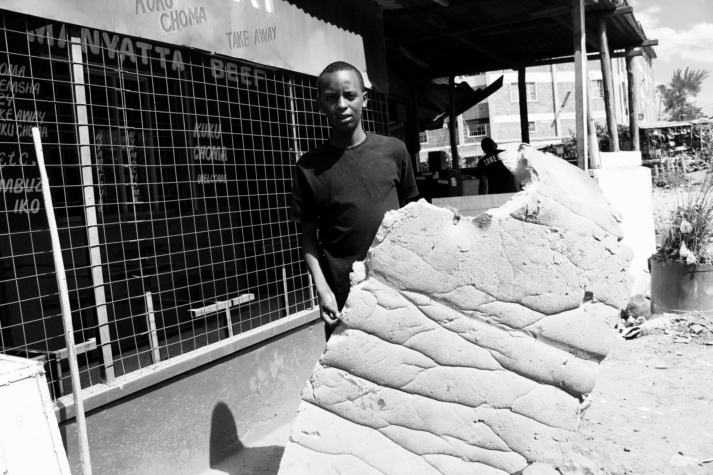 Boniface holding up a mattress the boys sleep on at night.