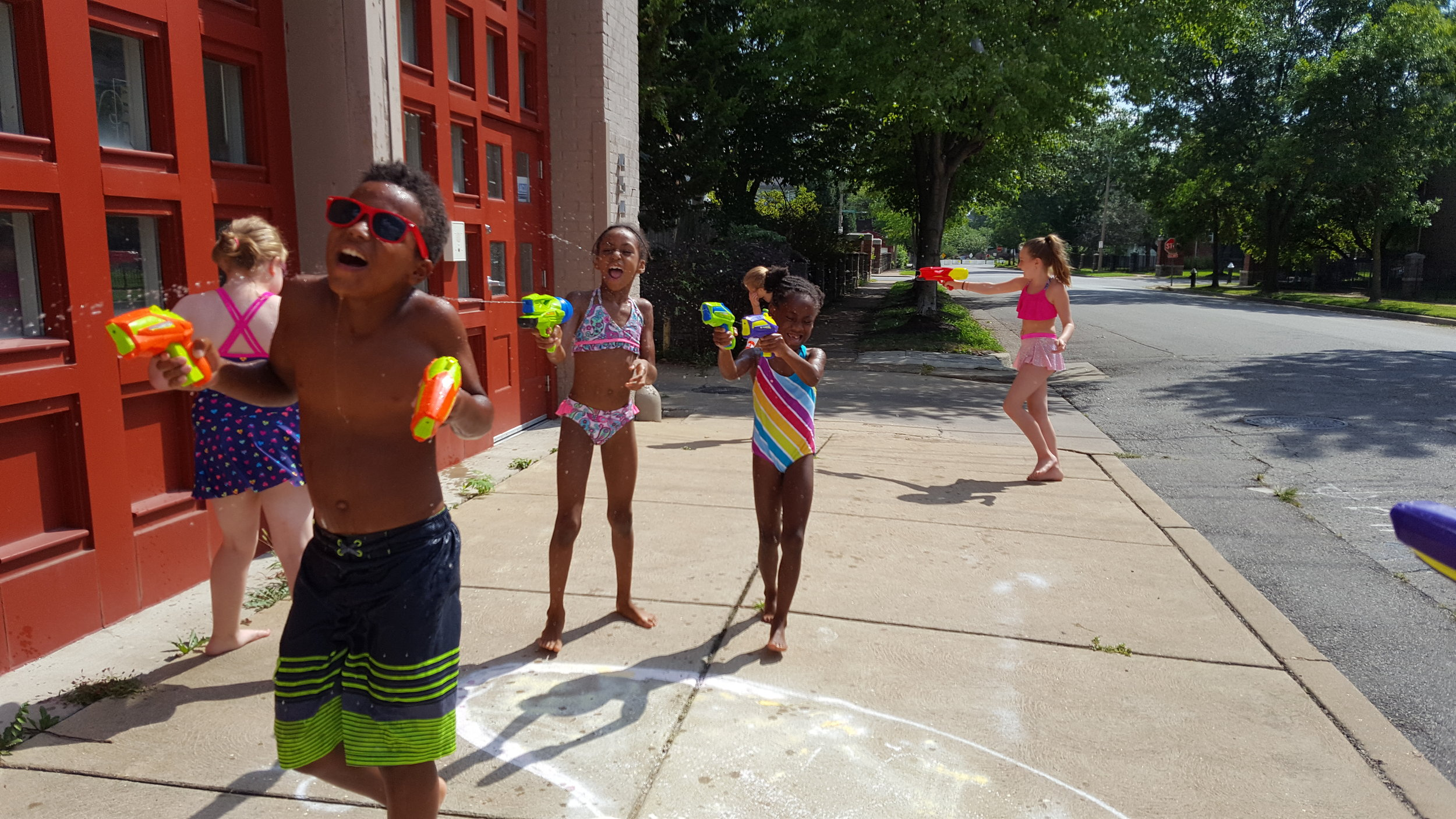 Kids cool off from the STL heat with a water-gun fight outside the studio!