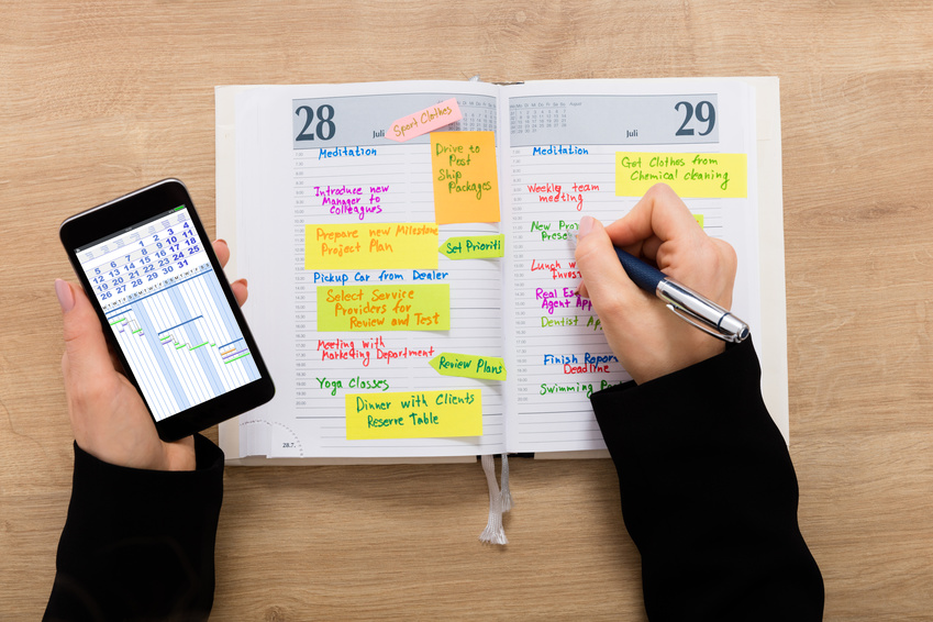 Businesswoman With Mobilephone Writing Schedule In Diary