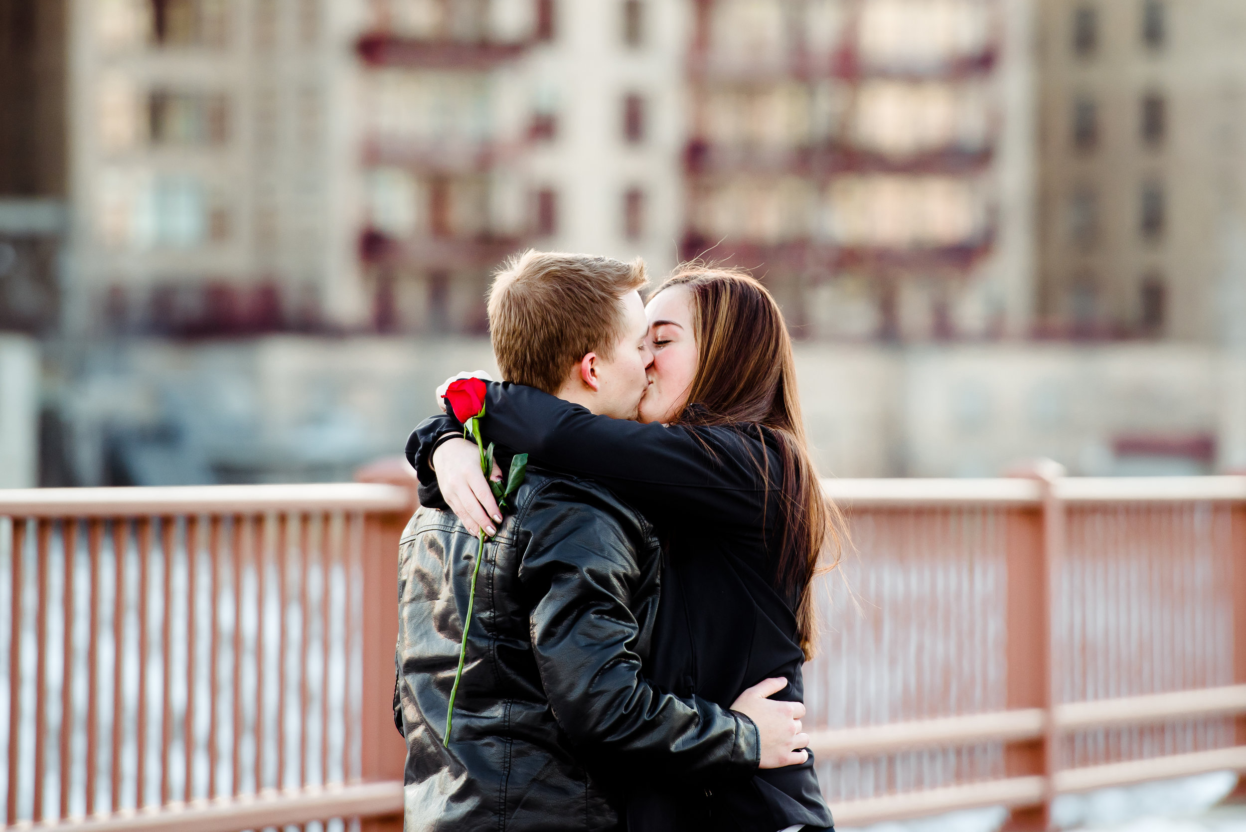 Marriage Proposal on the Stone Arch Bridge in Minneapolis - Romantic Kiss with Single Red Rose - Winter Engagement Minneapolis Proposal Photographer