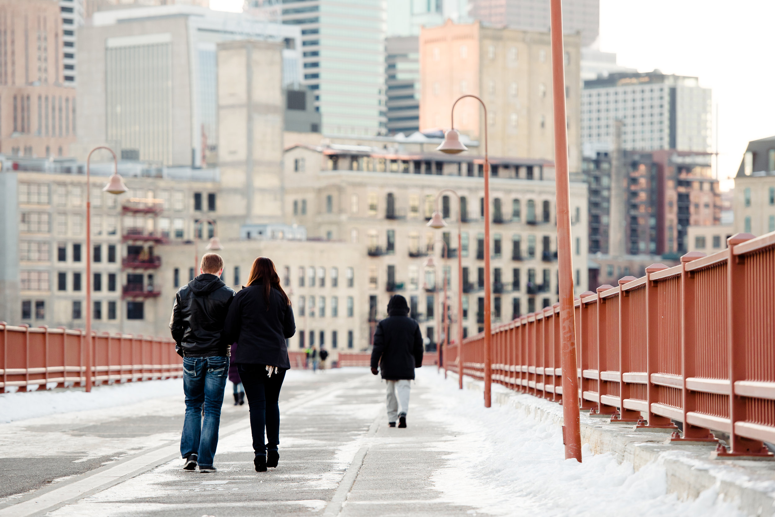 Stone Arch Bridge Proposal - Couple Walking at Sunset in the Winter Snow - MPLS Engagement Proposal Photography