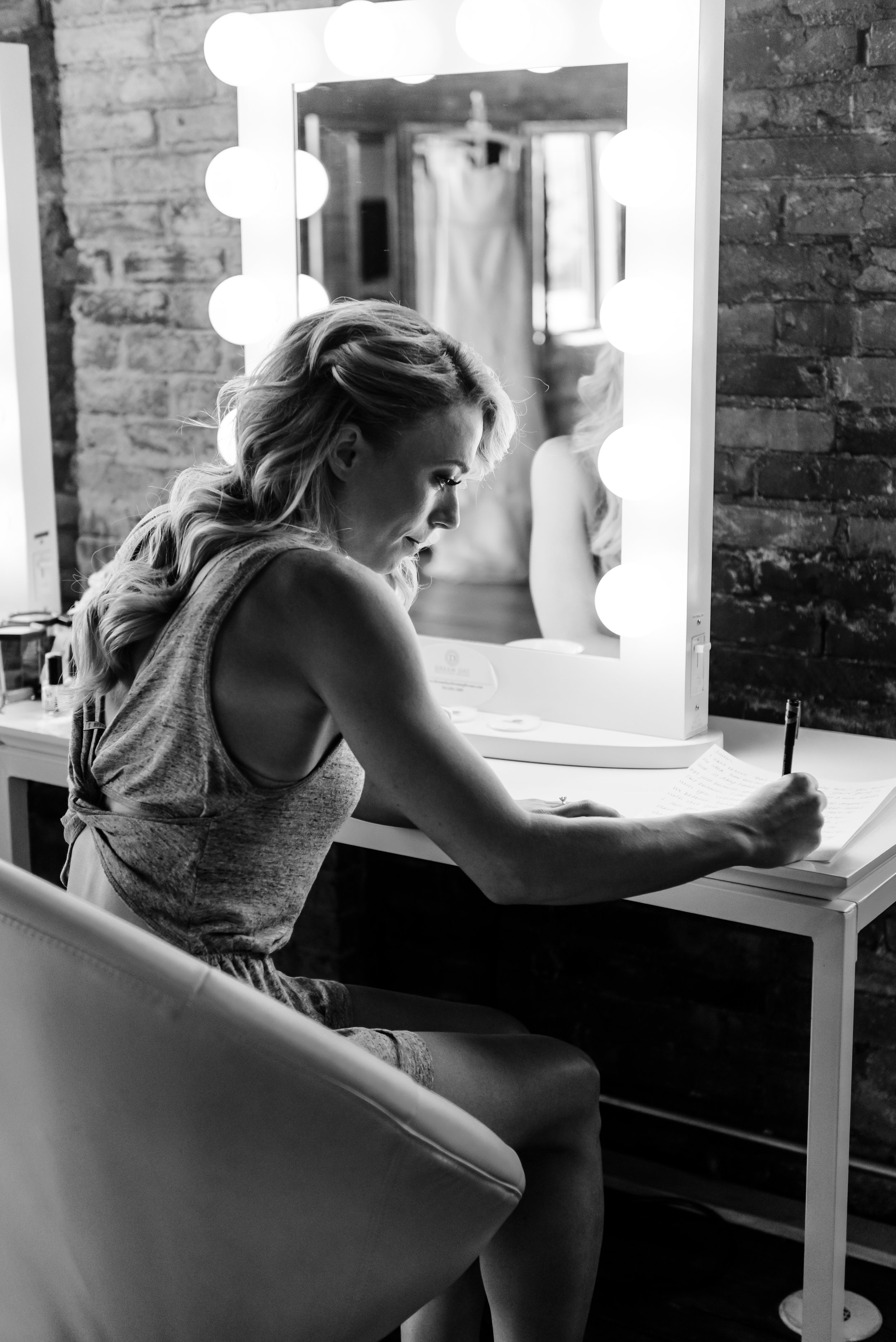 Bride writing letter to groom on wedding day - Laura Robinson Photography