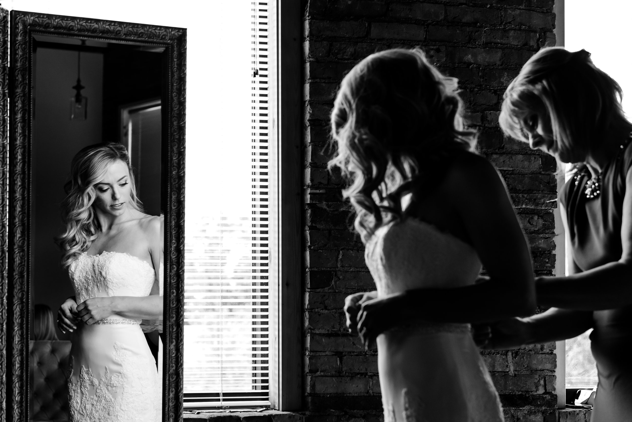 Mother helps bride into gown - Laura Robinson Photography