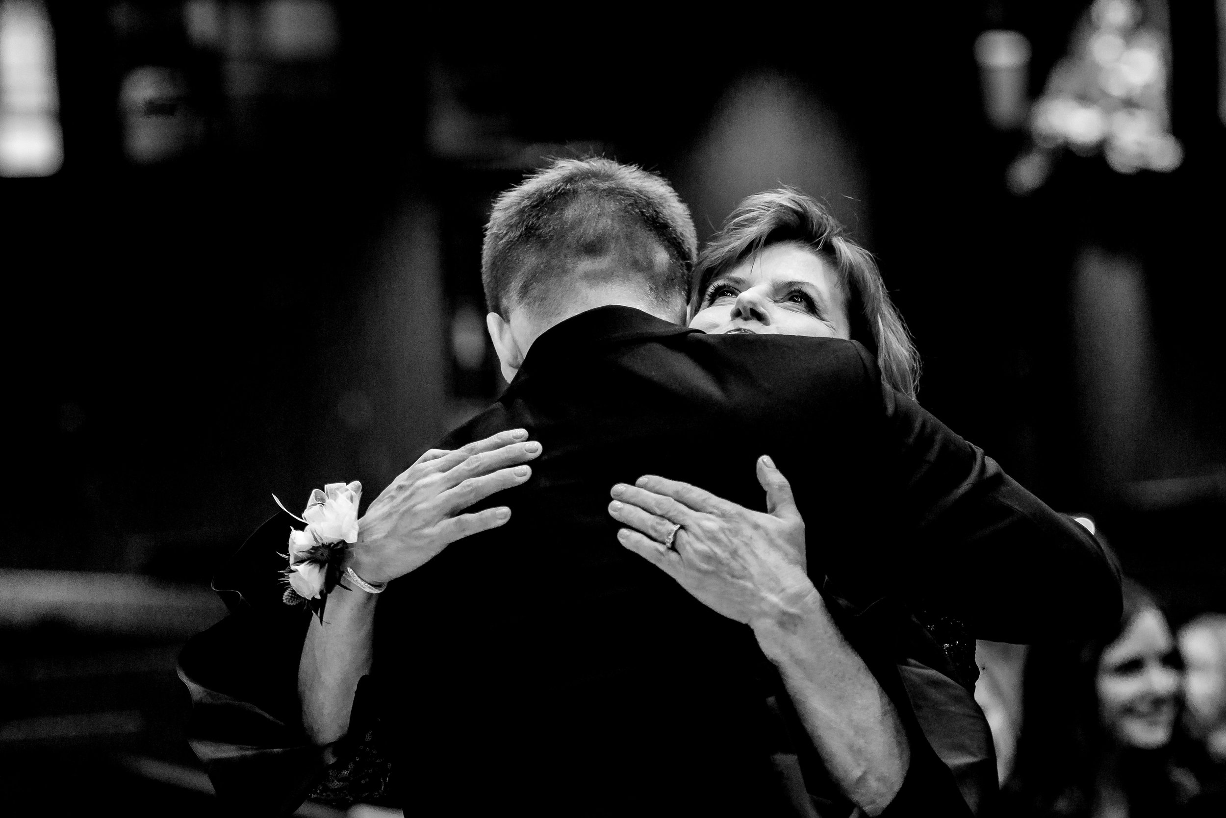 Mom Hugs Groom at St. Olaf Catholic Church in Downtown Mpls MN - Minneapolis Wedding Photography