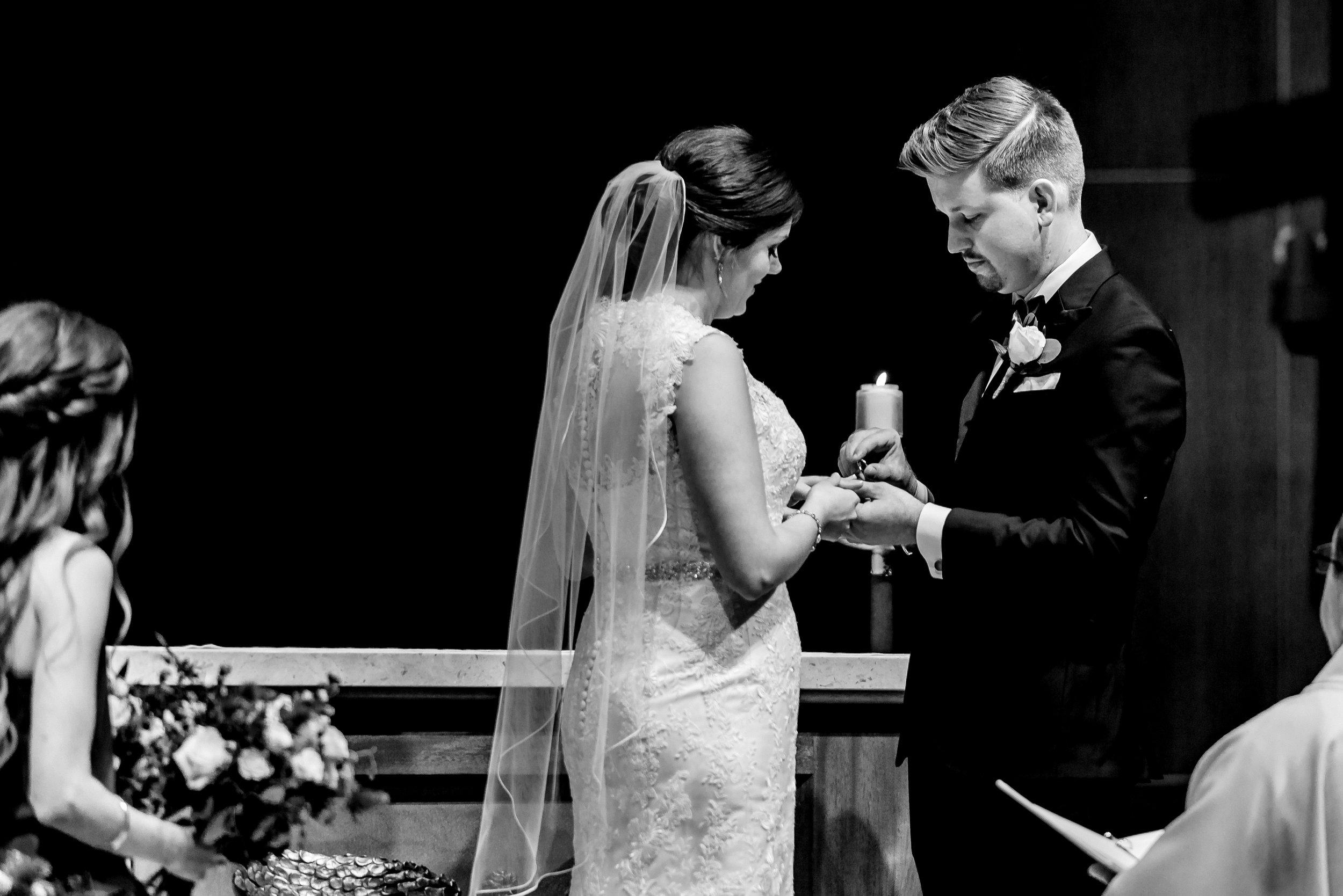 Groom Puts Ring on Bride's Finger - Wedding Ceremony at St. Olaf Catholic Church - Minneapolis Wedding Photojournalist